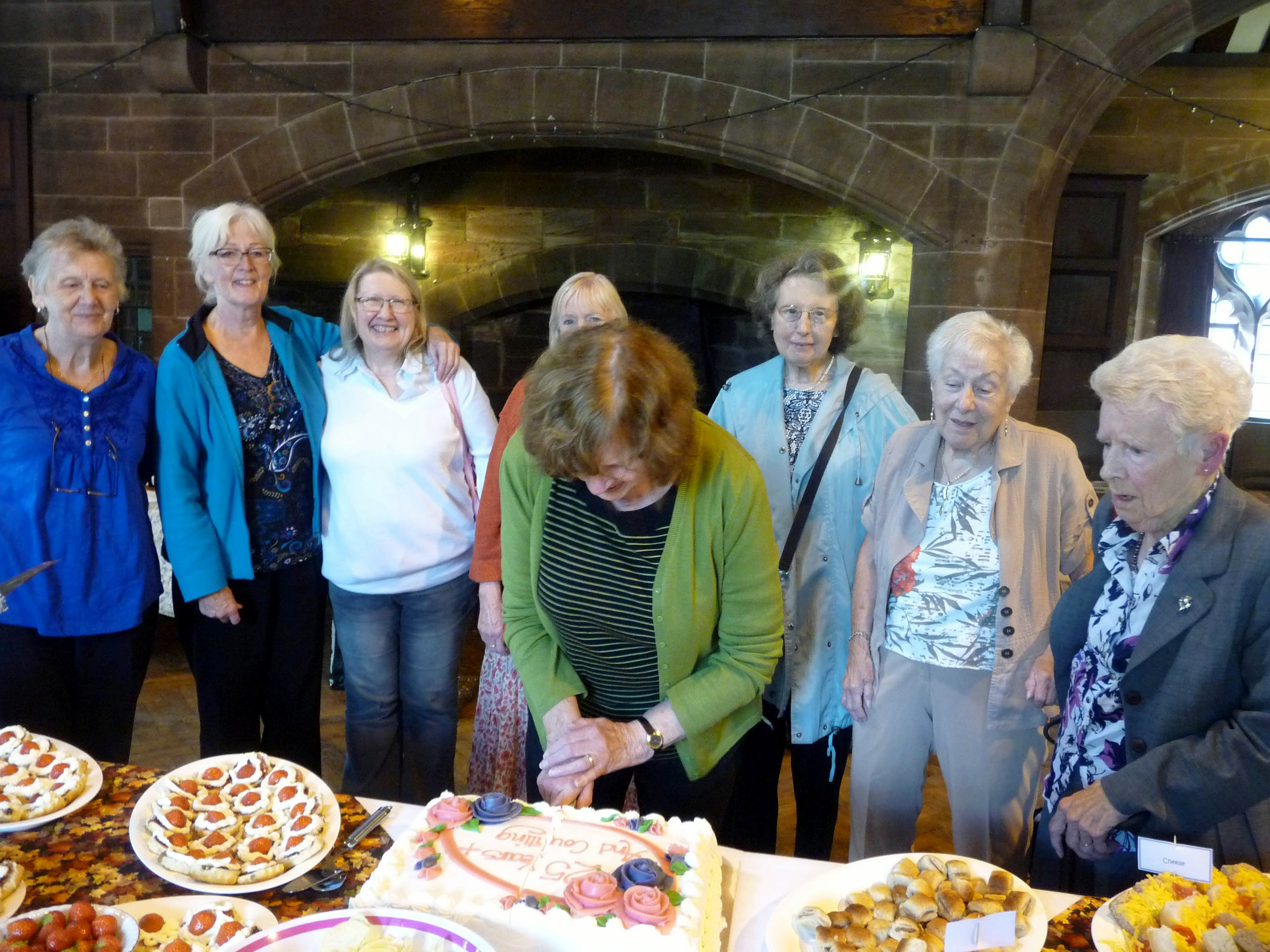 """Norma, who has been a MEG member for 40 years, cuts the """"25 Years Plus and Counting"""" cake at 2014 September Tea Party"""