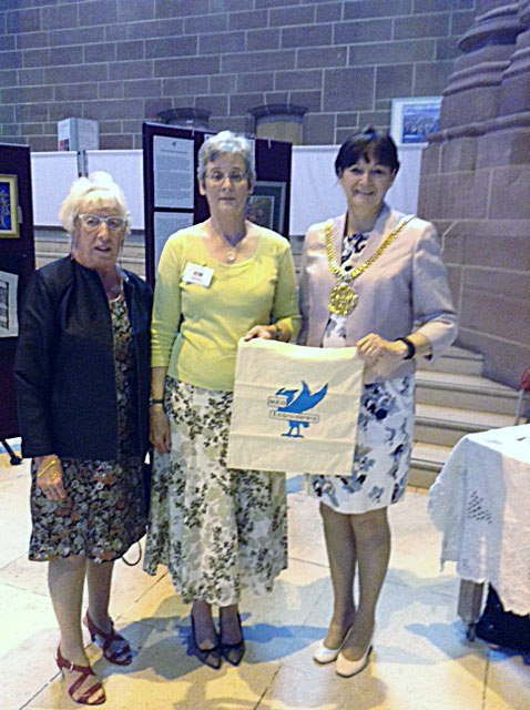 Rubina Porter MBE, Kim Parkman and Cllr. Roz Gladden, Lord Mayor of Liverpool with MEG cotton bag made in Sreepur at 60 Glorious Years exhibition in Liverpool Cathedral