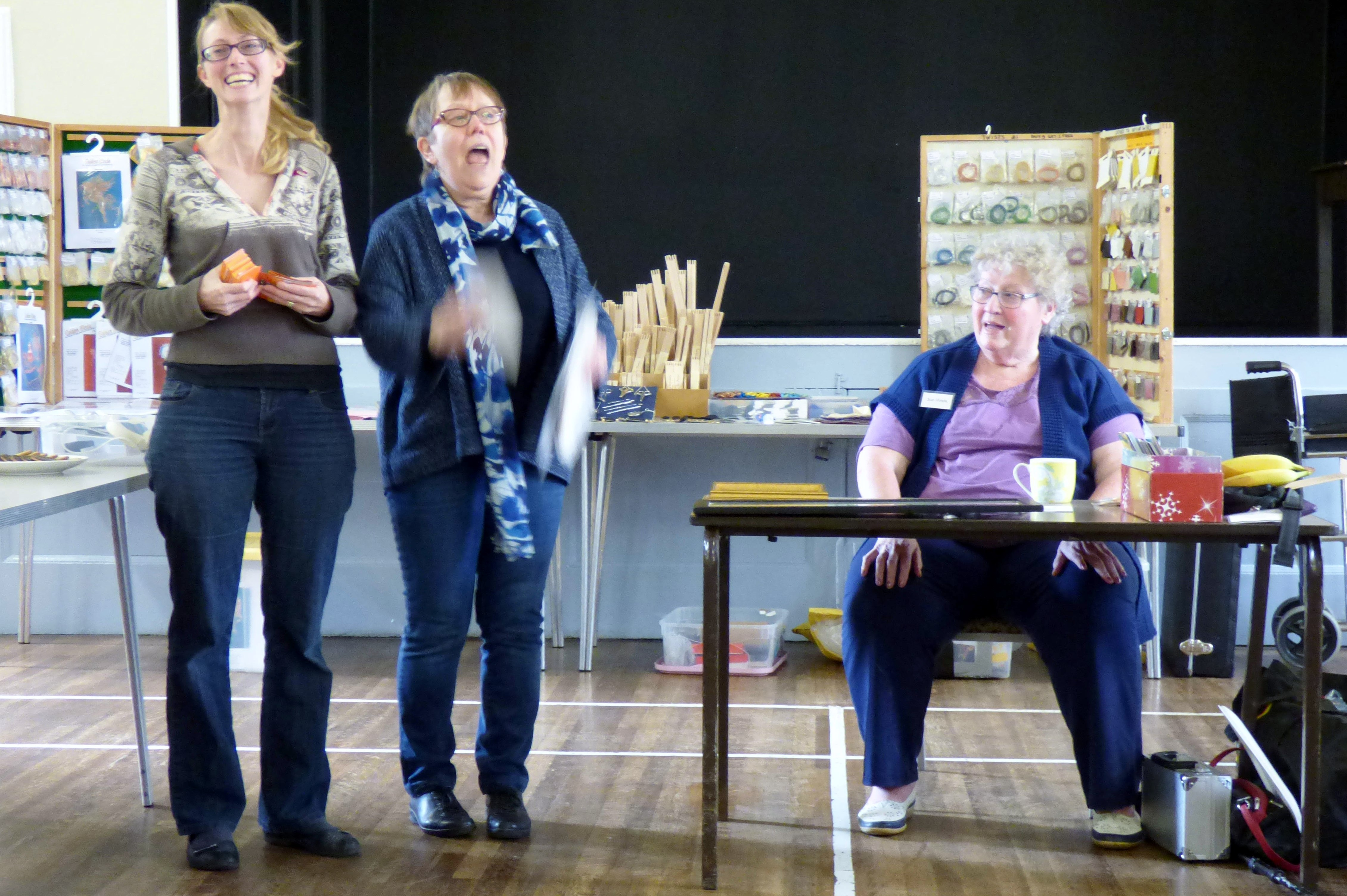 Marie is leading the group singing 'Happy Birthday' to Sarah Rakestraw at Or Nue Workshop with Golden Hinde