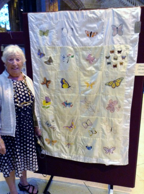 Rubina Porter MBE with butterfly silk embroidered quilt made by mothers and girls of Sreepur, with help from members of MEG, at 60 Glorious Years exhibition in Liverpool Cathedral 2016.