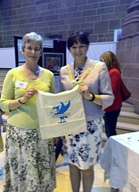 Kim Parkman and Cllr. Roz Gladden, Lord Mayor of Liverpool with MEG cotton bag made in Sreepur at 60 Glorious Years exhibition in Liverpool Cathedral