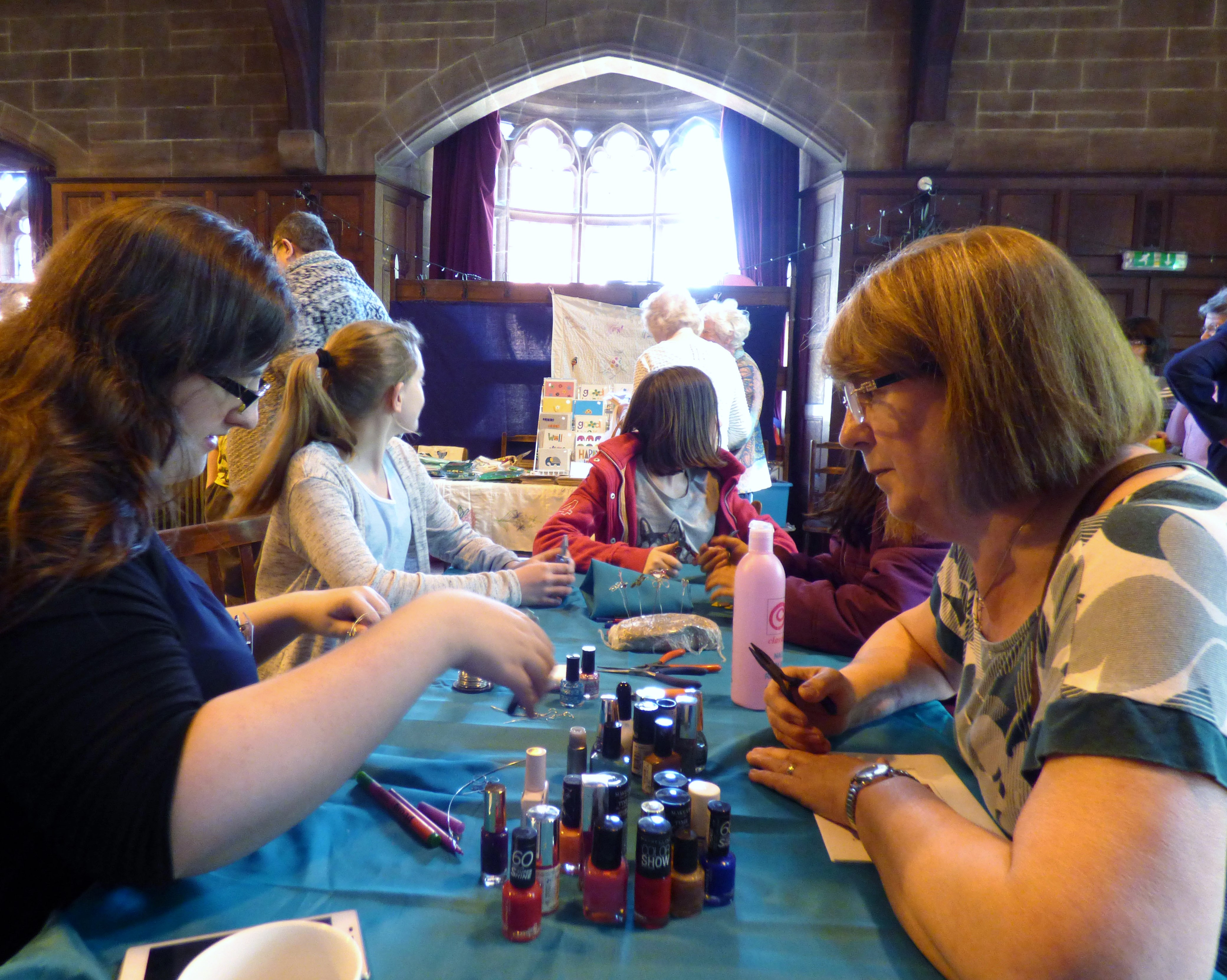 Sophie is demonstrating how to make wire butterflies at MEG Summer Tea Party 2016