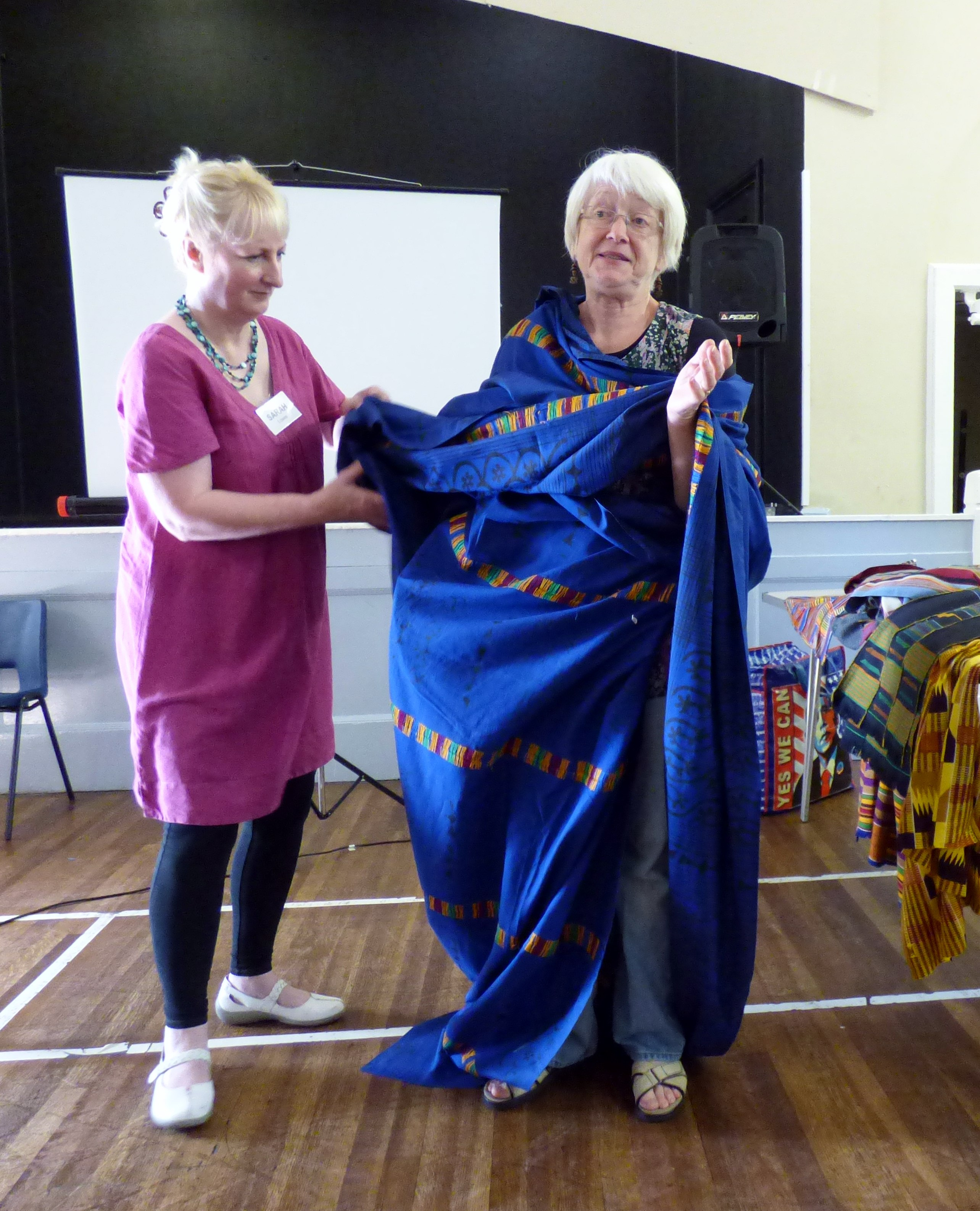 Magi Relph wearing a West African robe assisted by Sarah Lowes