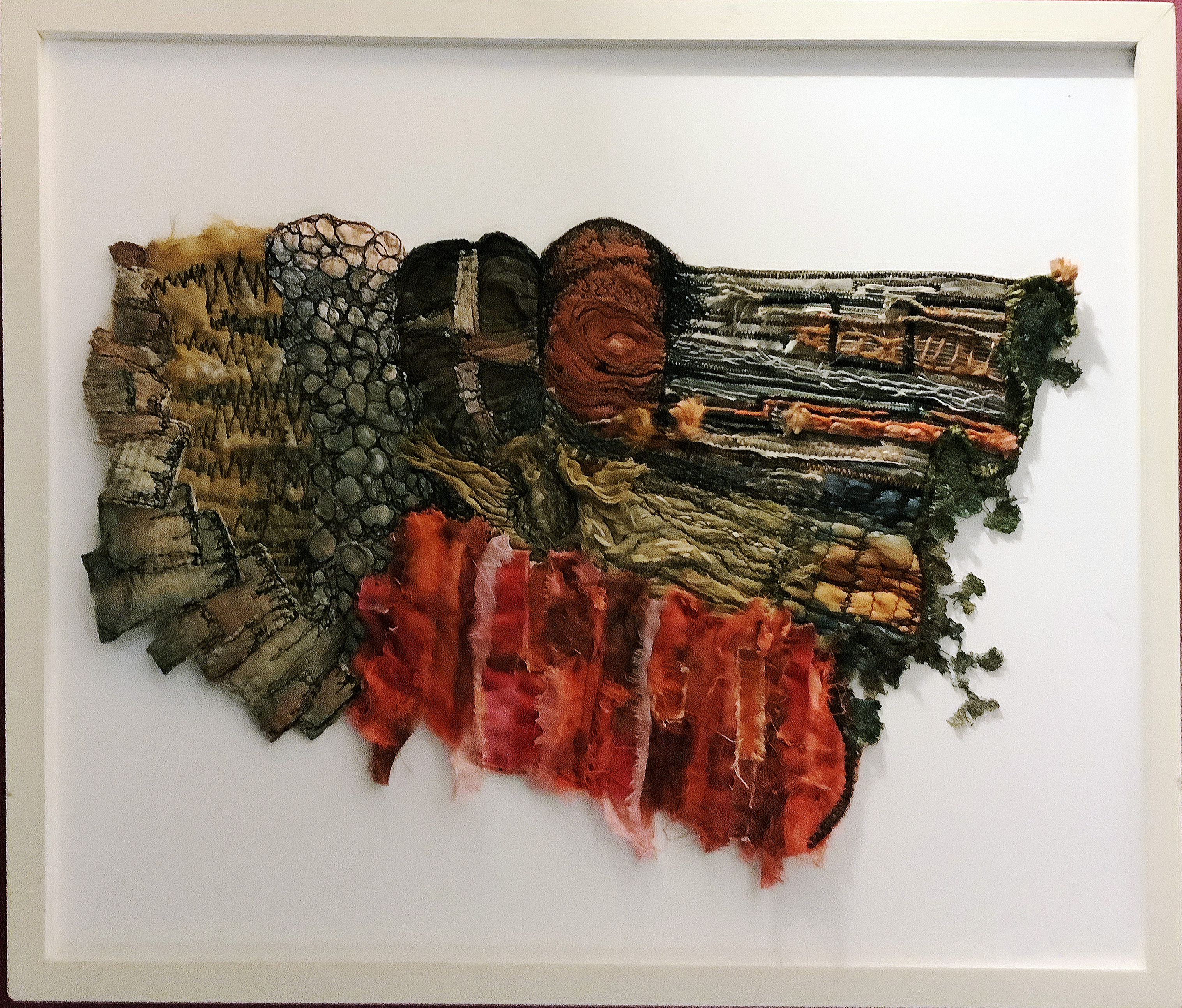 ABSTRACT SECTION OF A CLIFF FACE ANGLESEY by Brenda Brown, Bolton branch, hand dyed fabrics with couching, appliqué, fabric manipulation with hand and free machine stitching.