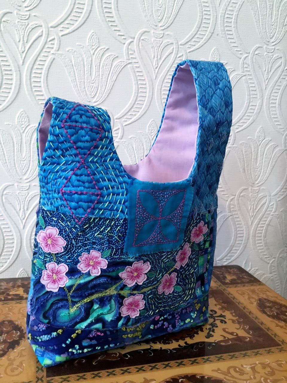 (back view)JAPANESE KNOT BAG by Sue Bennett, Lythom St. Annes branch, made using the Boro technique of applying patches with hand and machine embroidery. The chrysanthemum and cherry blossom were machine stitched and hand painted, Aurifil competition 2021