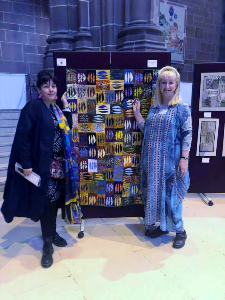 Sarah Lowes and friend with Sarah's quilt GUM LEAVES IN THE OUTBACK, reverse applique,  Endeavour exhibition, Liverpool Cathedral, Sept 2018