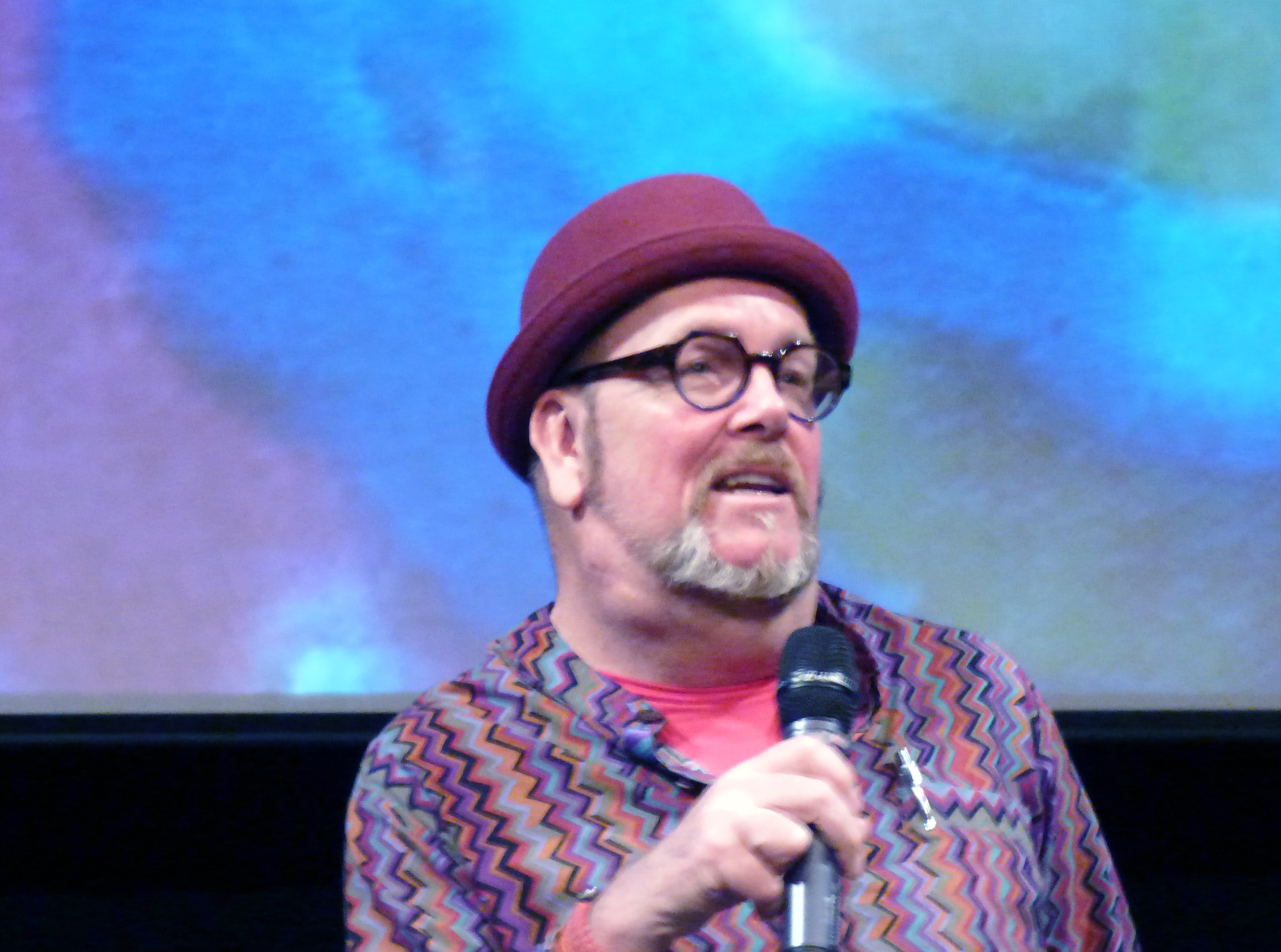Brandon is telling the audience about Kaffe Fassett at Kaffe Fassett Lecture, Capstone Theatre, Dec 2016
