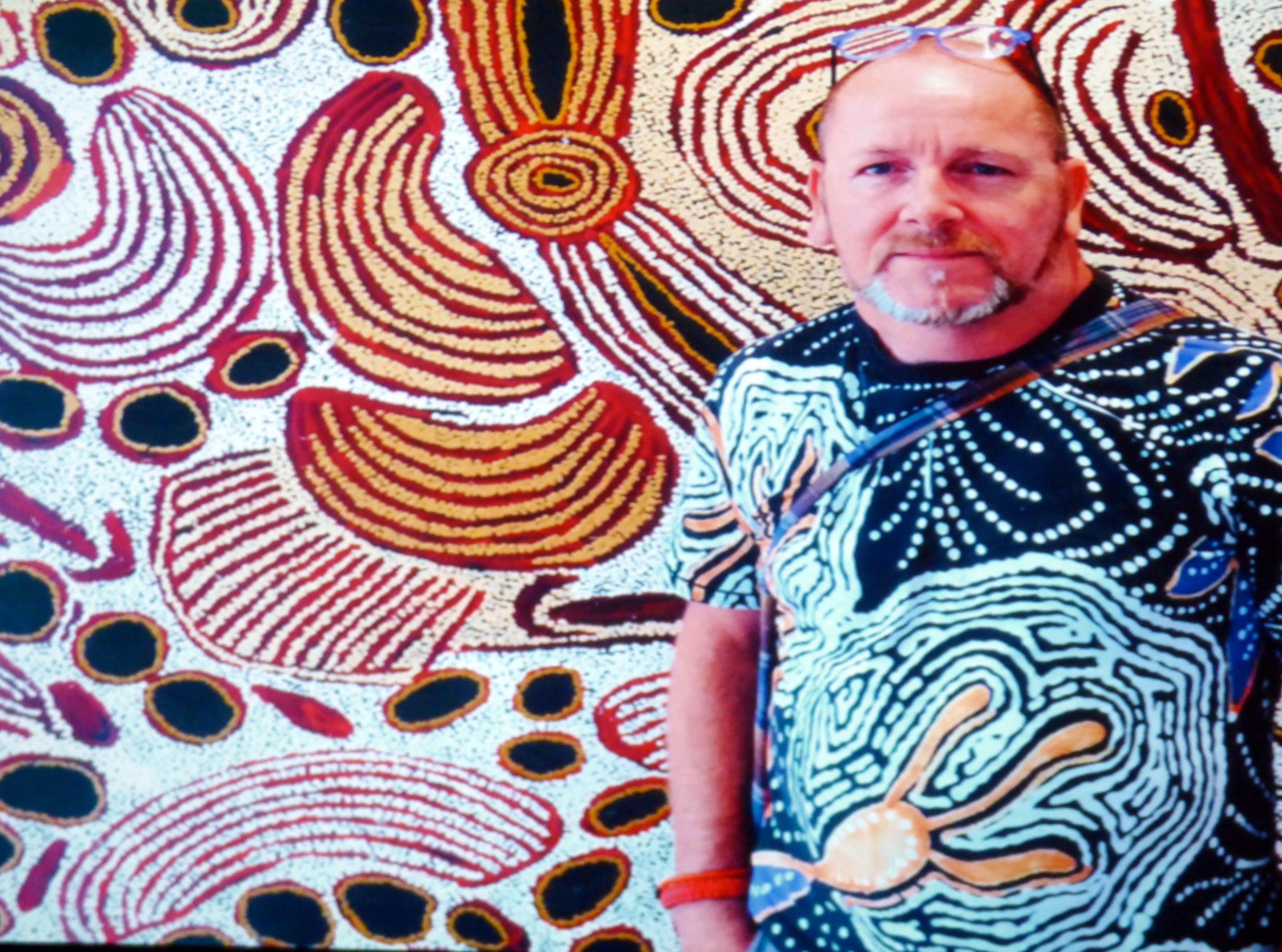 slide showing Brandon with Aborigine art at Kaffe Fassett Lecture, Capstone Theatre, Dec 2016