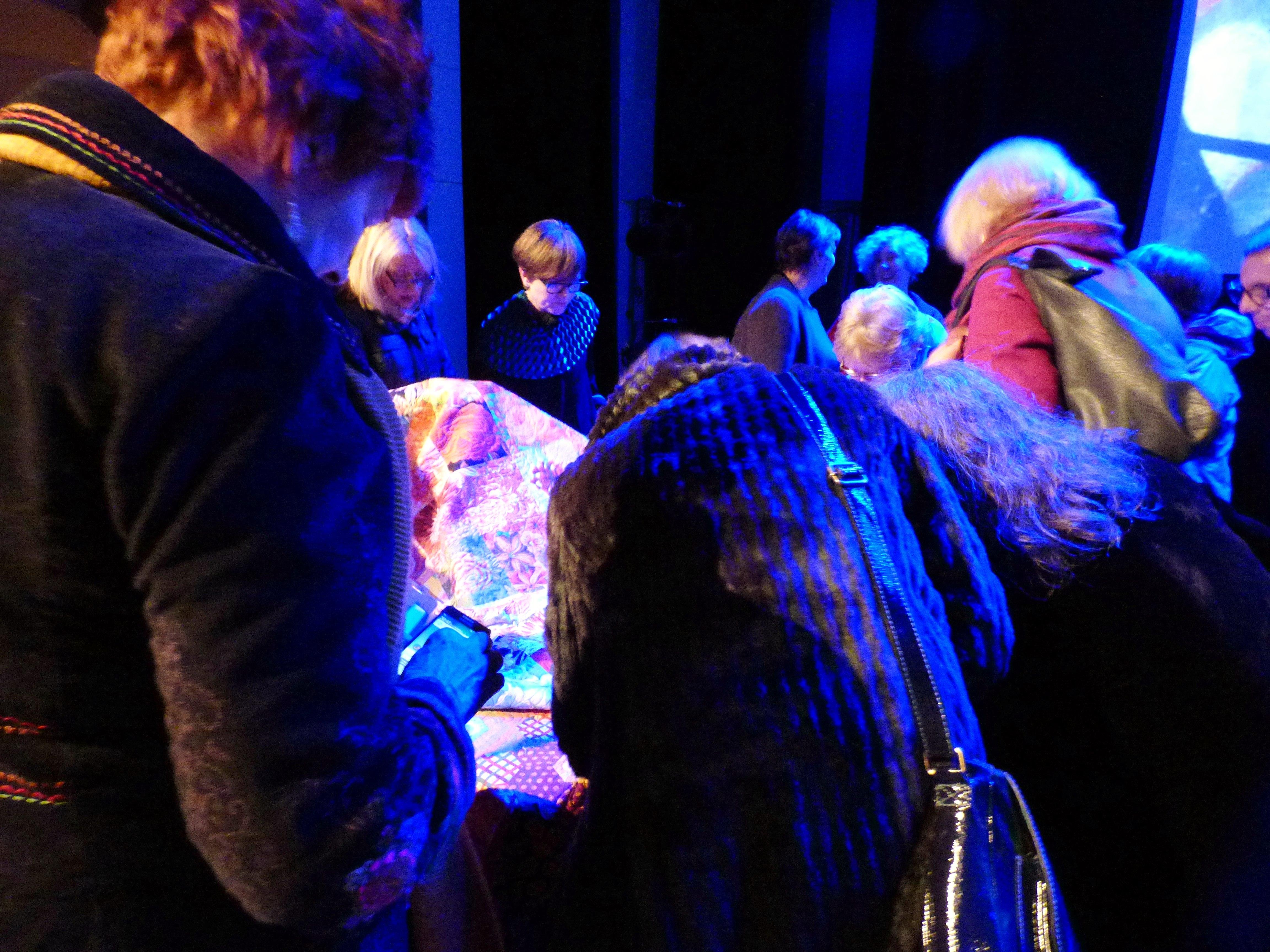 an admiring crowd with a Kaffe Fassett quilt, Kaffe Fassett Lecture, Capstone Theatre, Dec 2016