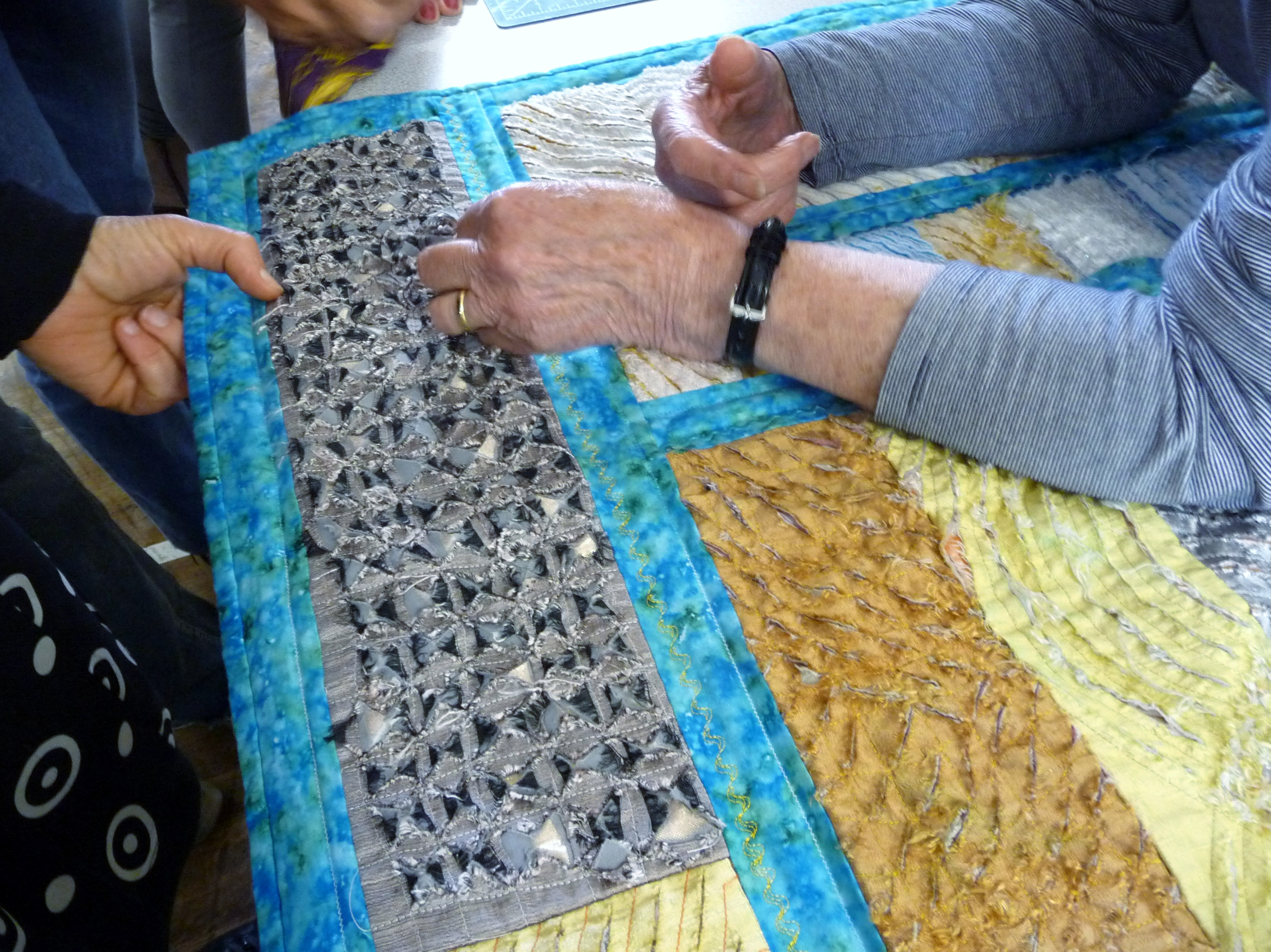 students are examining 'chenille' fabric quilt made by Norma Heron