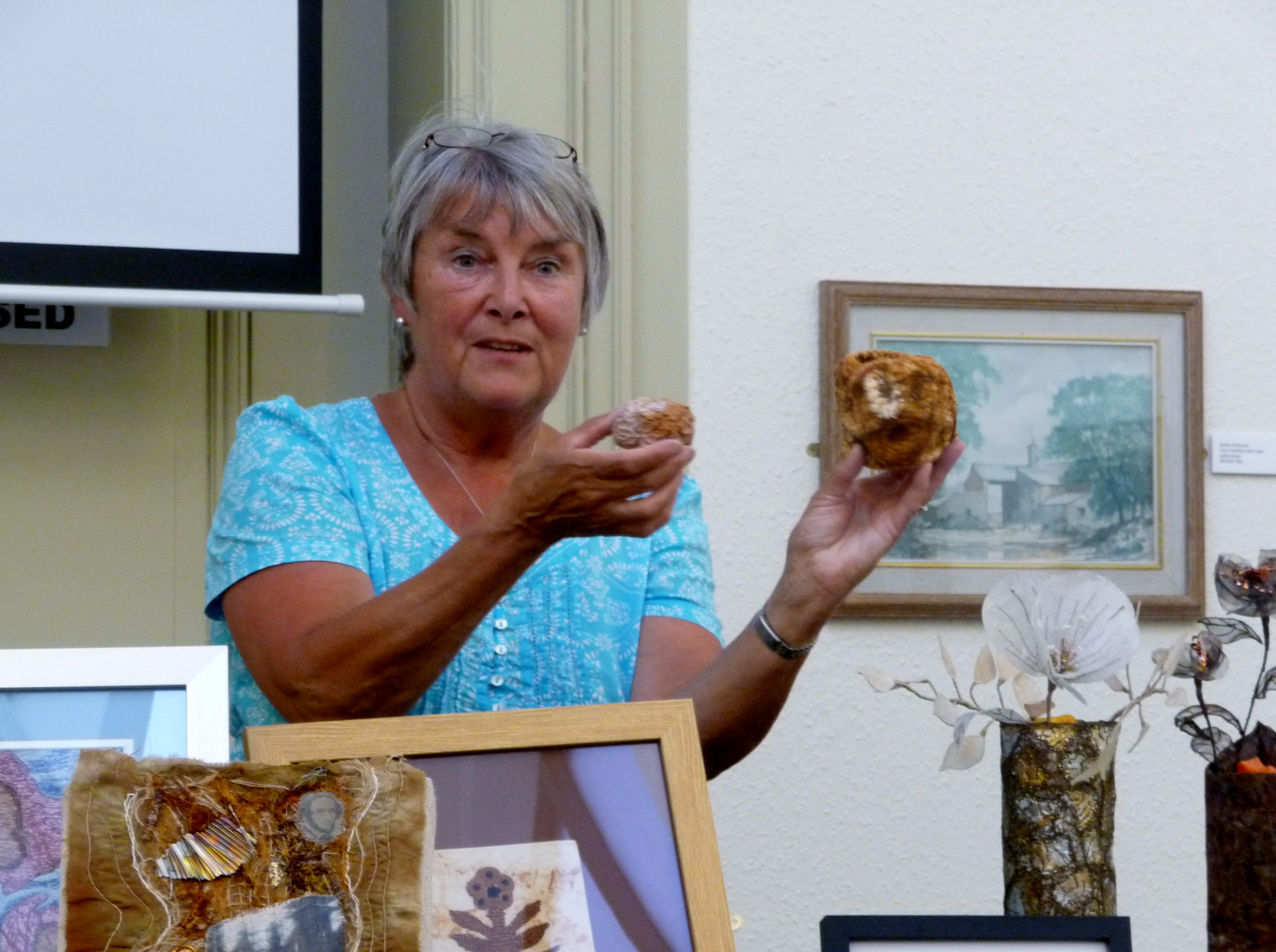 Moya McCarthy displaying SEED PODS made from rusted wire with hand stitching