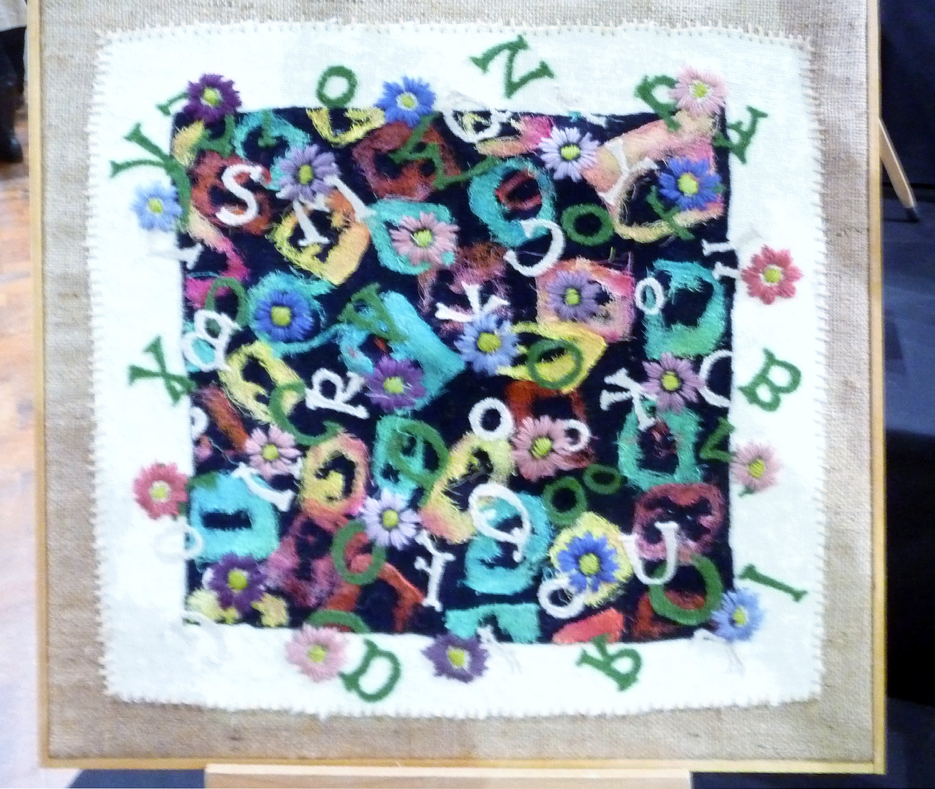 SAY IT WITH FLOWERS by Jane Jenkins, reclcled cheesecloth, knitted garments & blanket on hessian