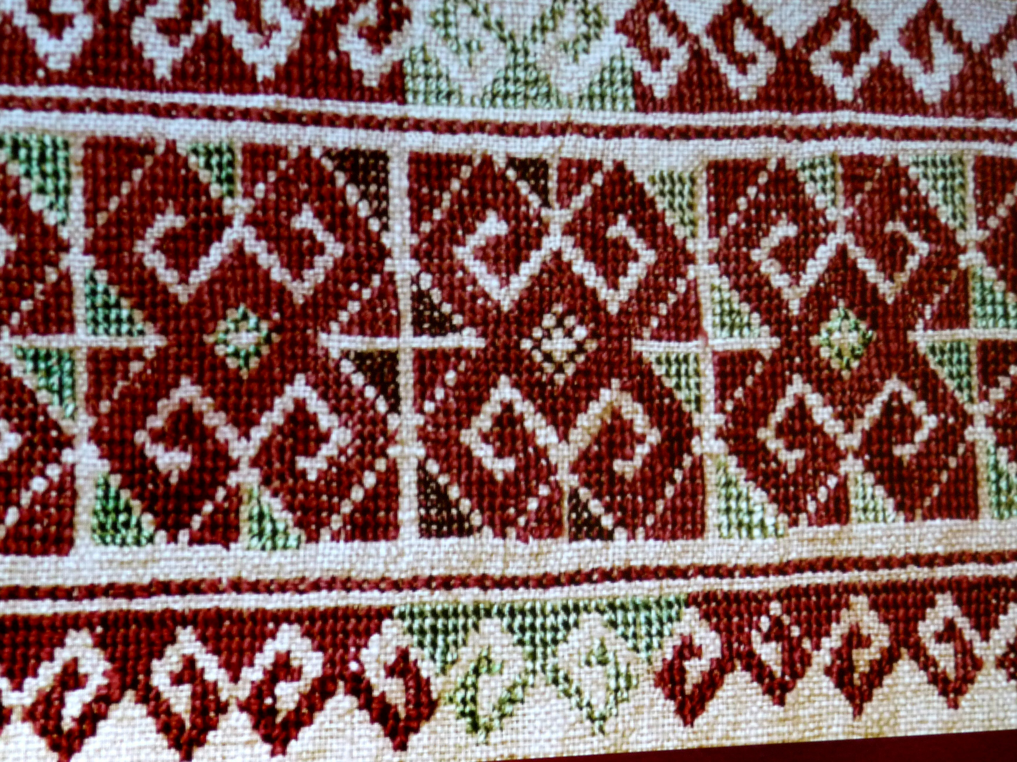 slide showing detail of embroidered clothing by  Qaraqalpaq people