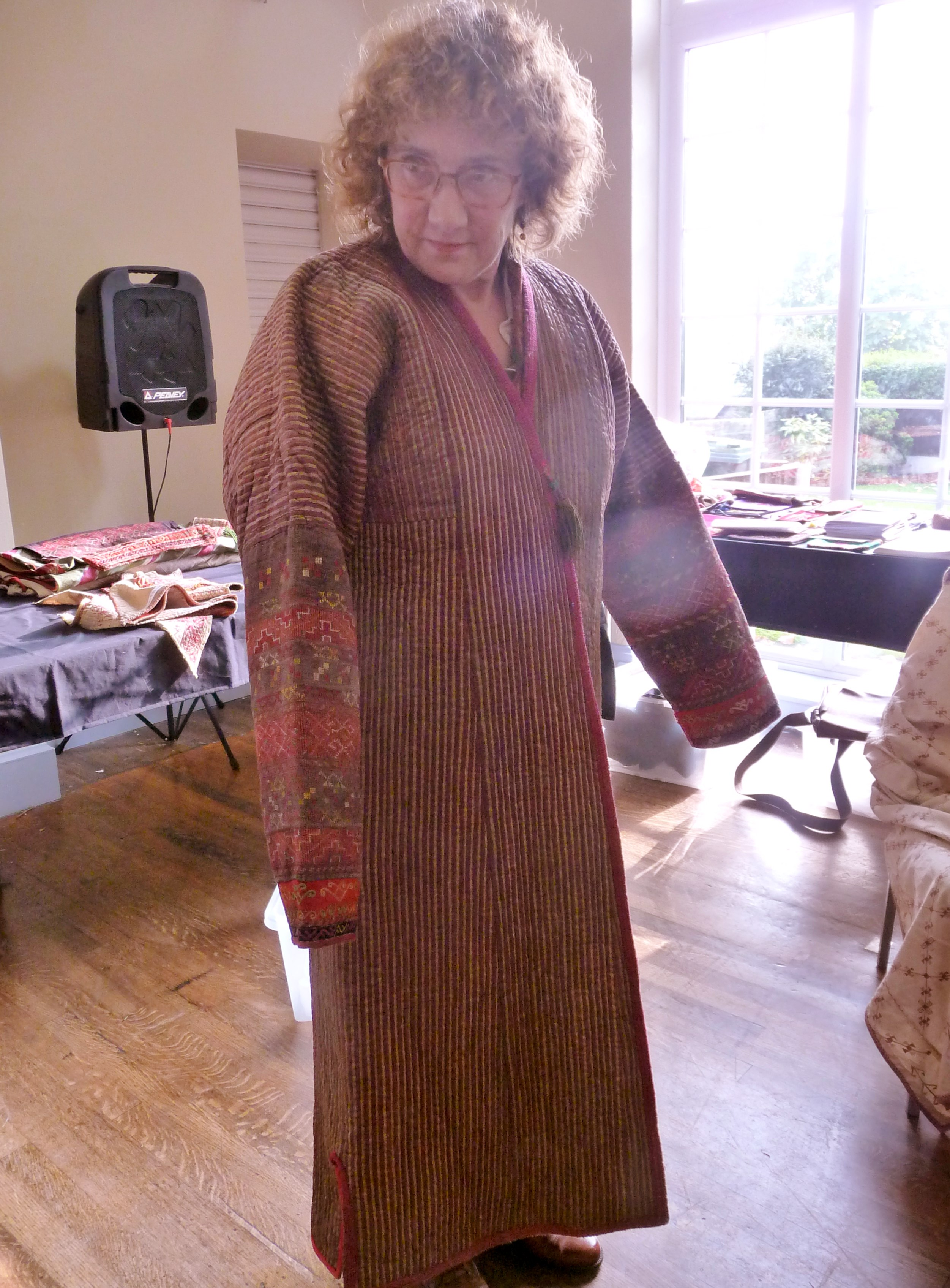 Sue Richardson is wearing a padded embroidered coat made by Qaraqalpaq people. The sleeves are designed to be over long