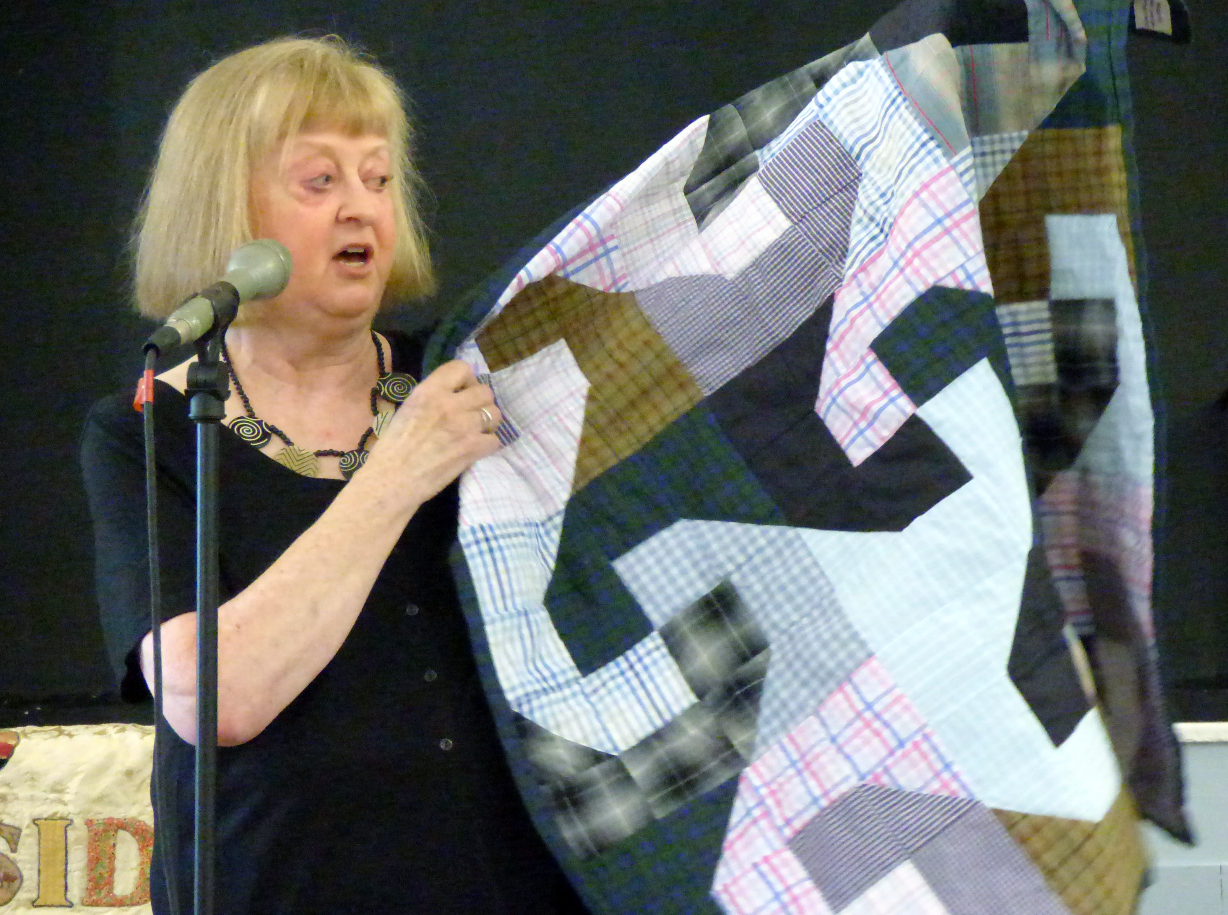 Caroline Fogell with a quilt made from men's shirts at Talk by Caroline Fogell from Project Linus
