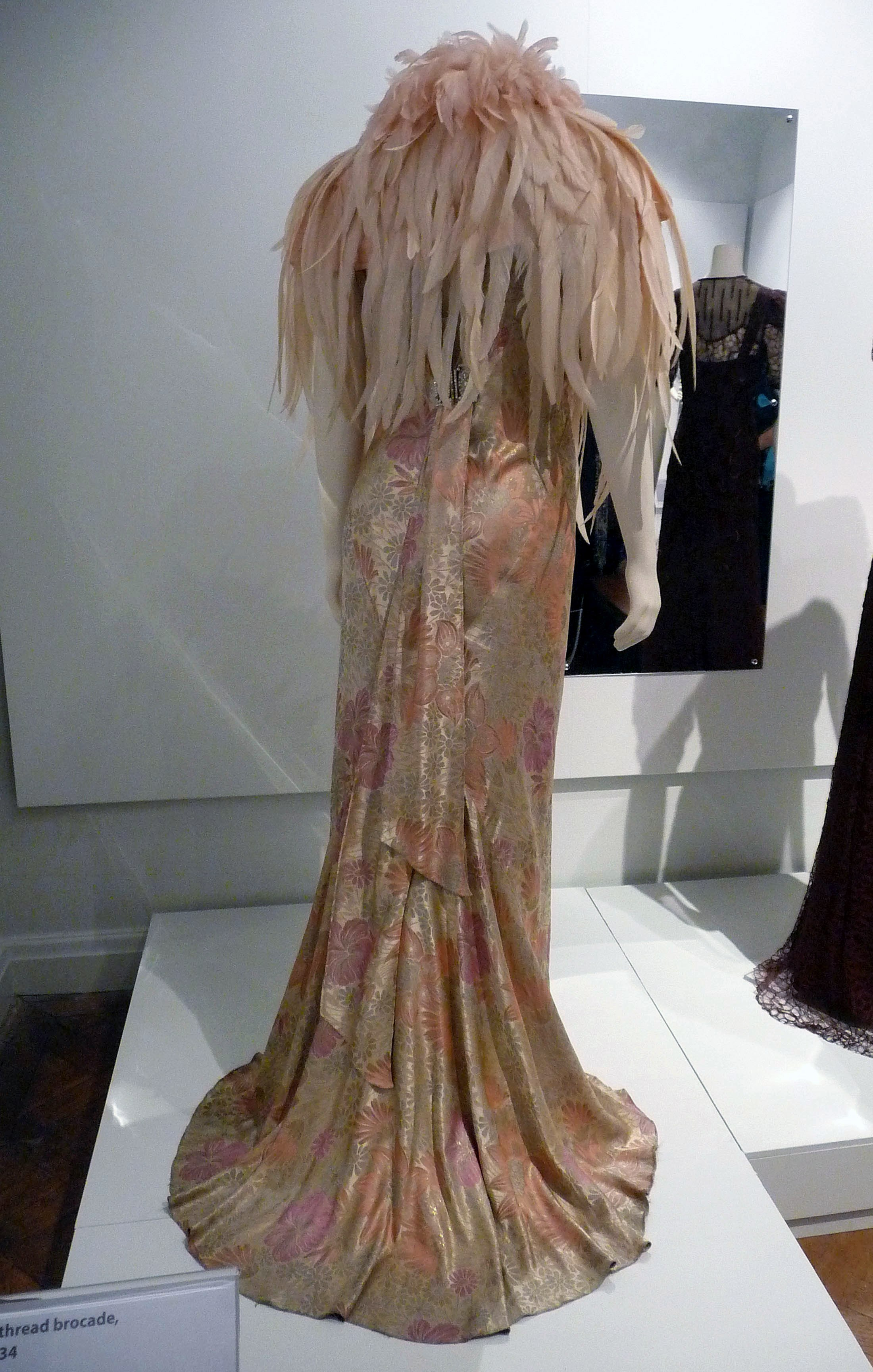 Evening dress, silk & metal thread brocade, 1934. Shoulder cape, silk & dyed cock's feathers, 1932-34