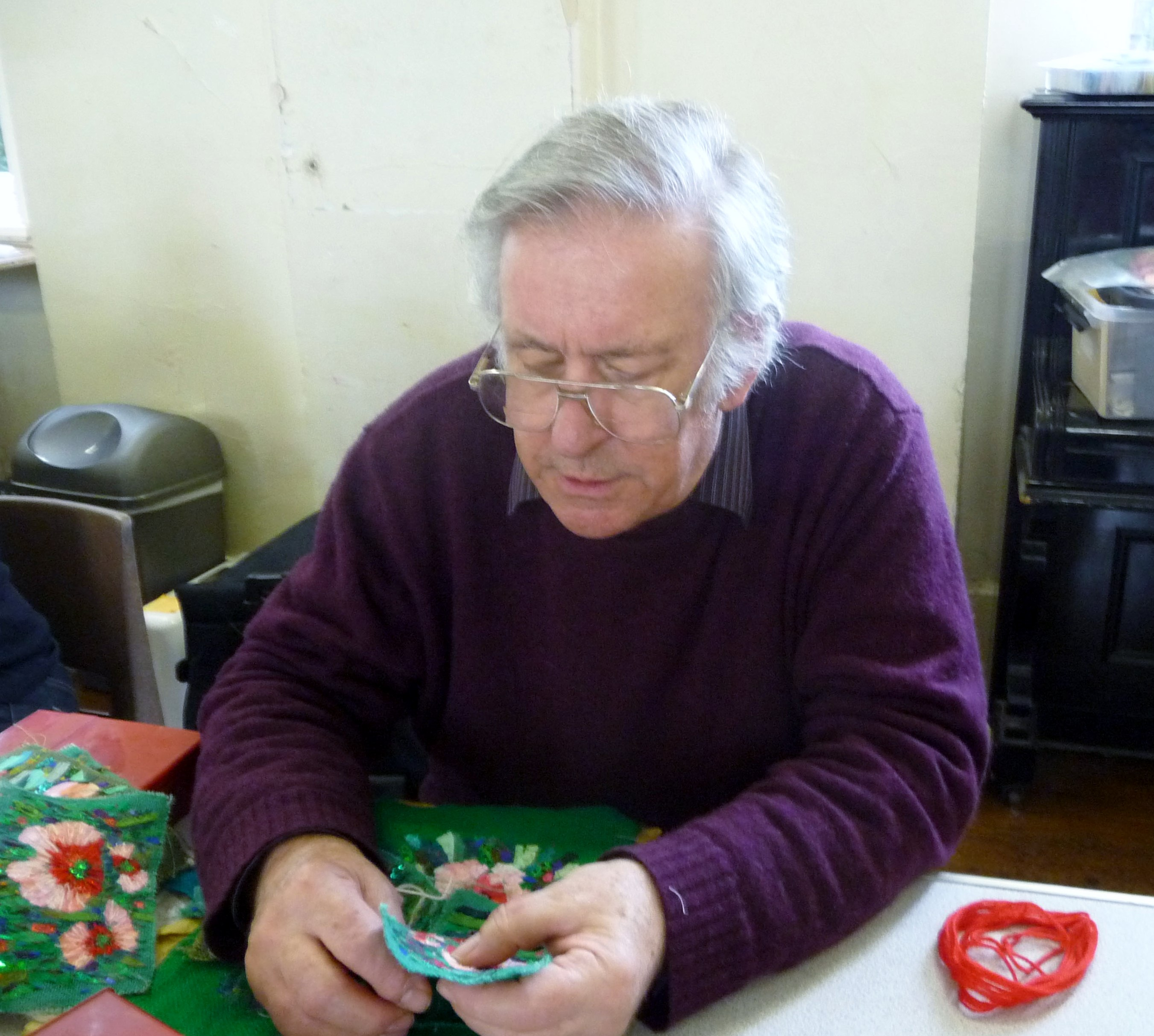 "Richard Box is demonstrating how to hand stitch the flowers at ""Poppies"" workshop at MEG"