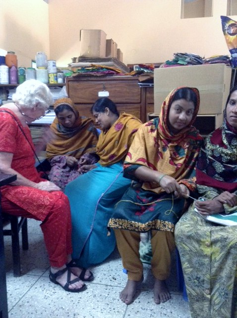 Ruby Porter MBE is showing some of the Sreepur women how to make the new glasses strings