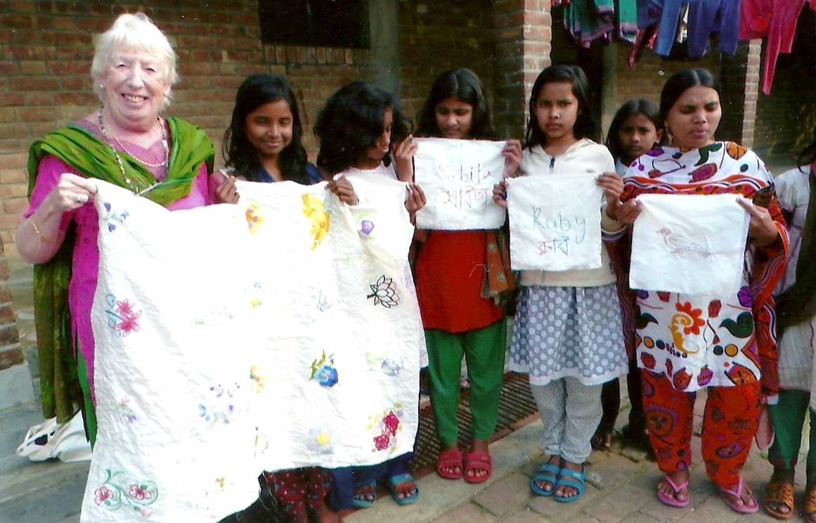 Ruby in Sreepur Village, Bangladesh with the flower quilt and some of young embroiderers who made the squares for the quilt which was jointly completed with Merseyside Young Embroiderers