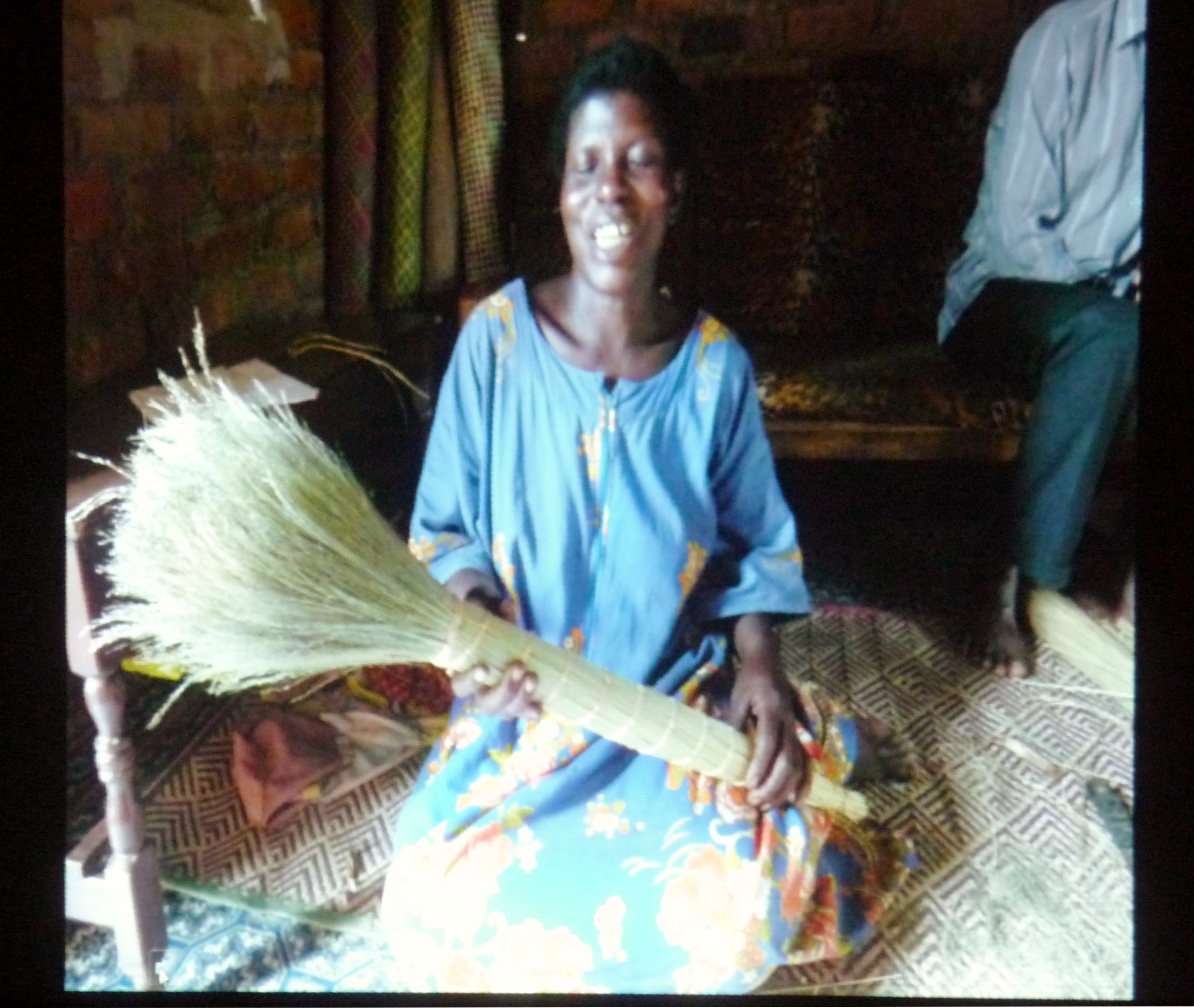 slide by Bobby Britnall showing a Ugandan woman holding a completed broom