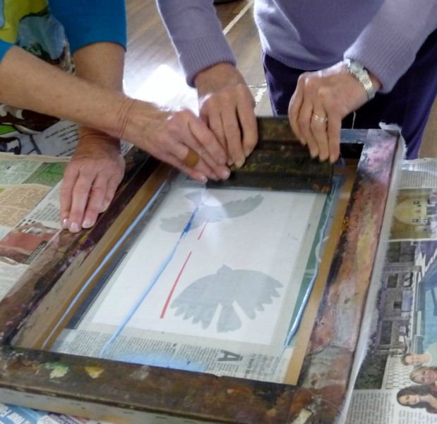 Elsie is showing one of the group the correct technique for screen printing