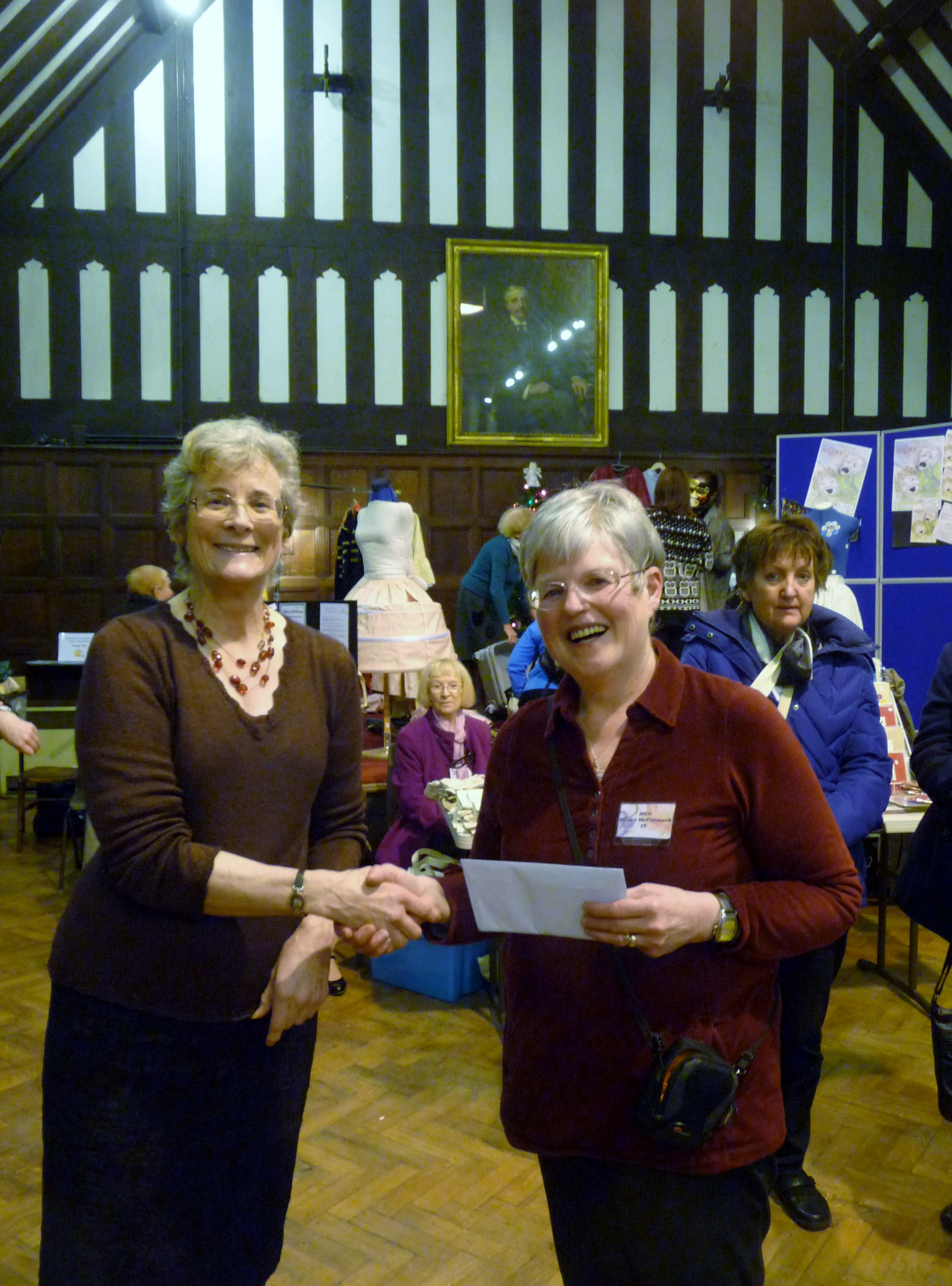 Hilary McCormack, winner of Traditional Embroidery competition 2014, receiving her prize from MEG Chair Kim Parkman at MEG Christmas party 2014