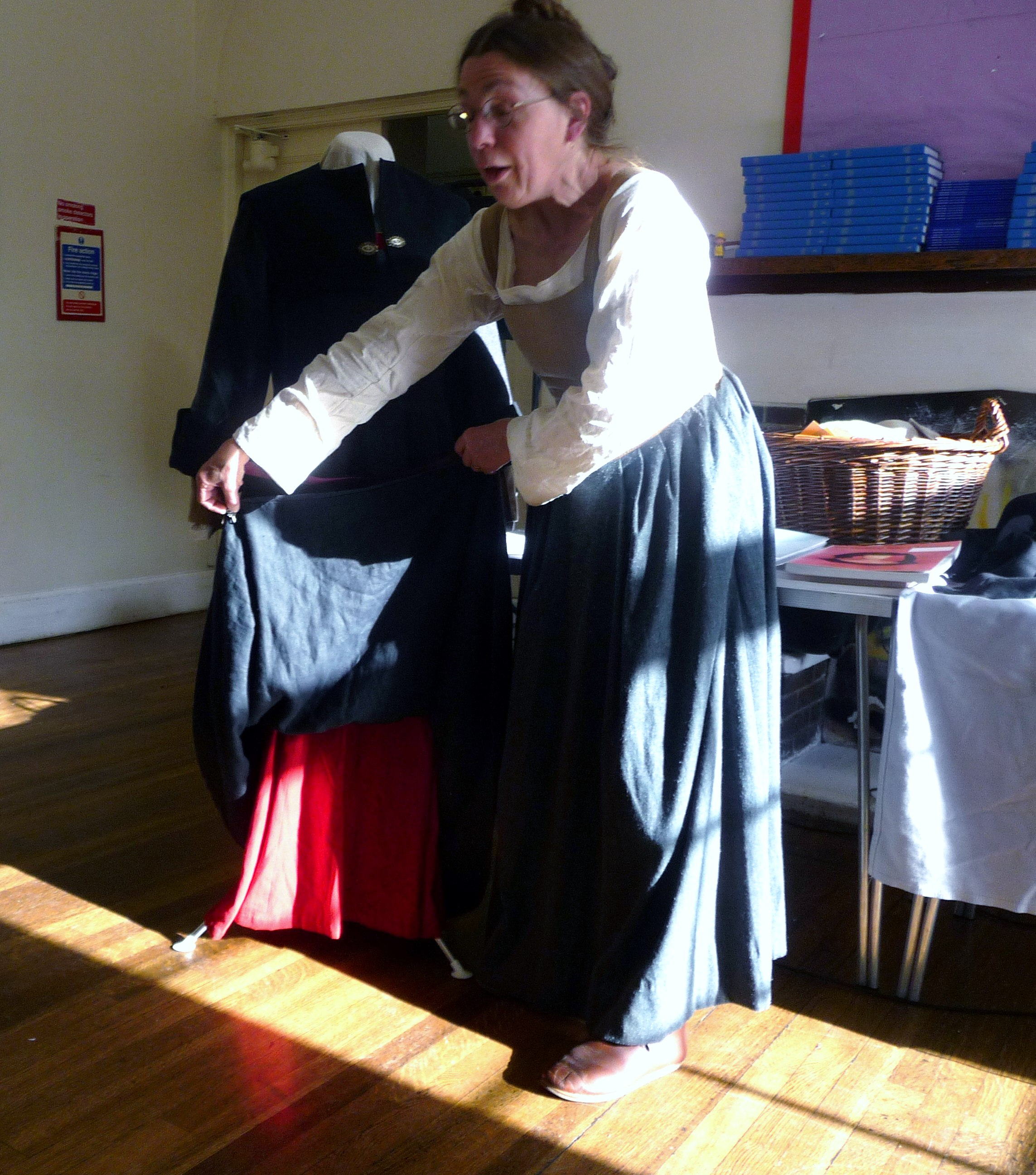 Sarah Thursfield is demonstrating a skirt lifter which was fastened to the gown to show the red petticoat