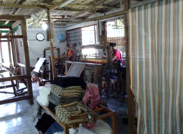 A loom in the new weaving shed, Sreepur, Bangladesh. Weavers are making striped fabric.