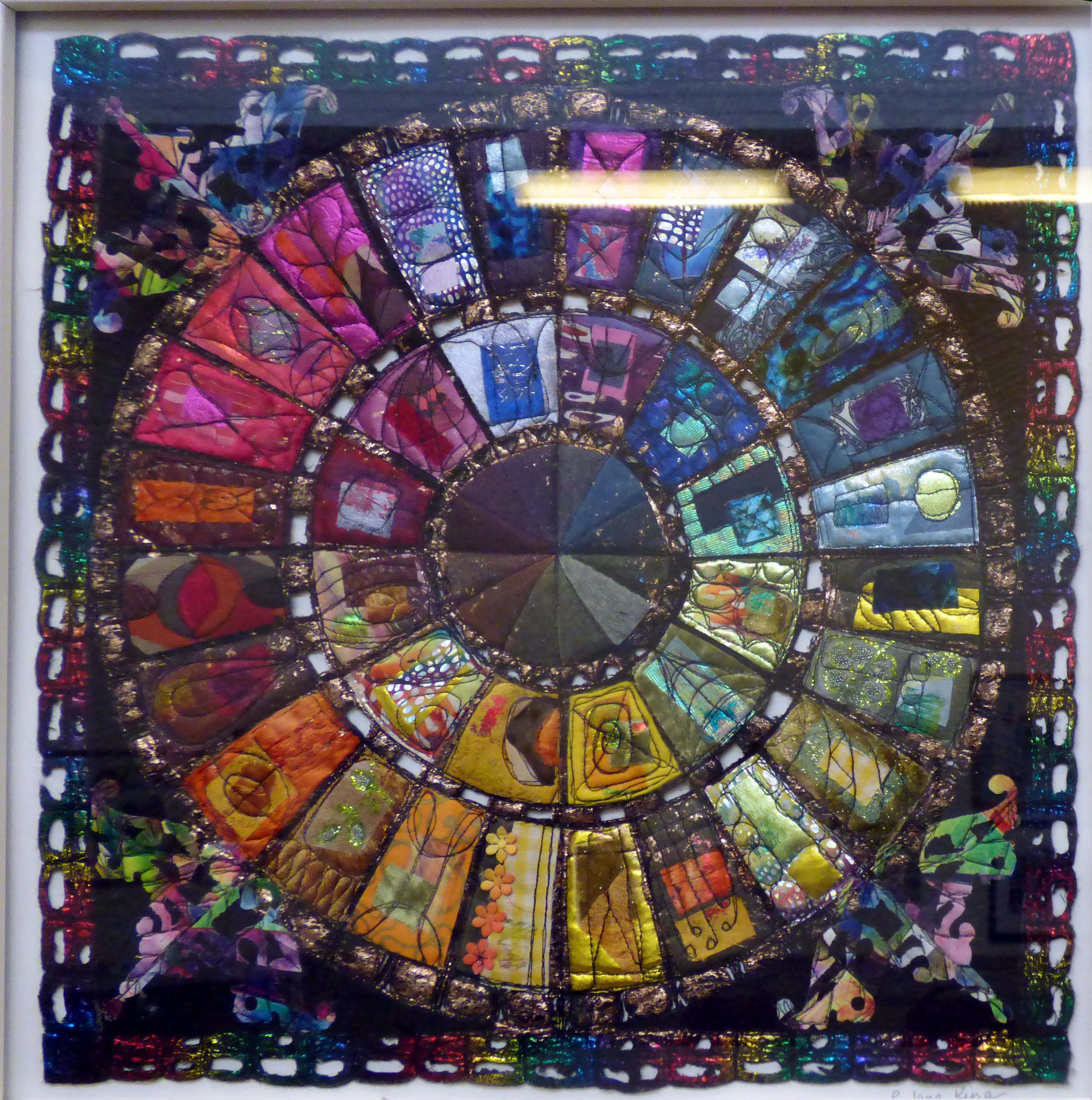 COLOUR WHEEL ROSE WINDOW by Patricia Jane King, mixed fabrics, foils and threads constructed with machine stitching and soldering iron