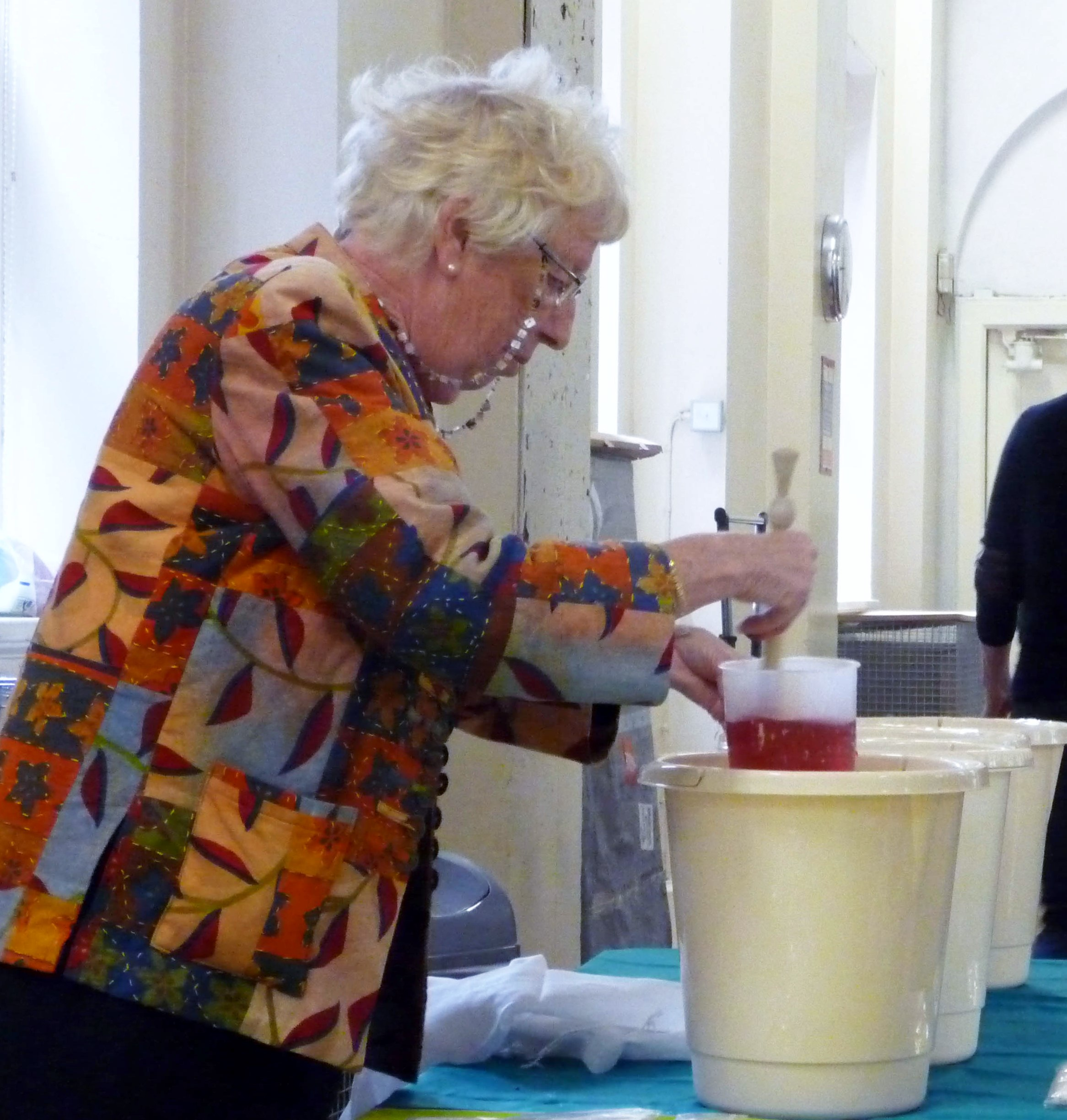 Ruby Porter MBE is mixing some dyes. We are going to dye Sreepur scarves