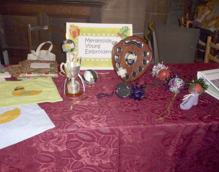 the Young Embroiderers\' table with the Cup and Shield for the YE member who has made the most improvement during the year