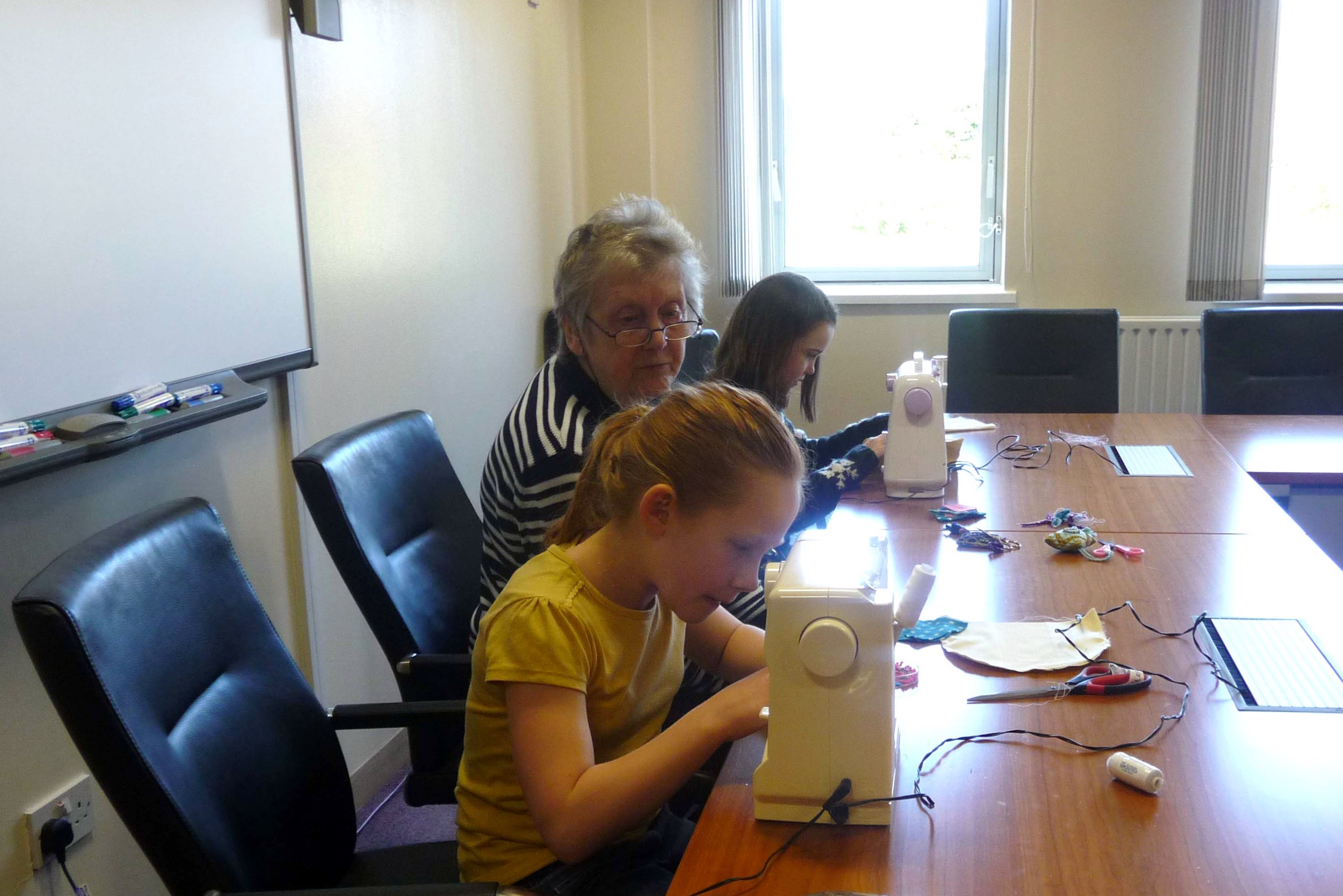 Val is helping Zoe and Ruby with machine sewing