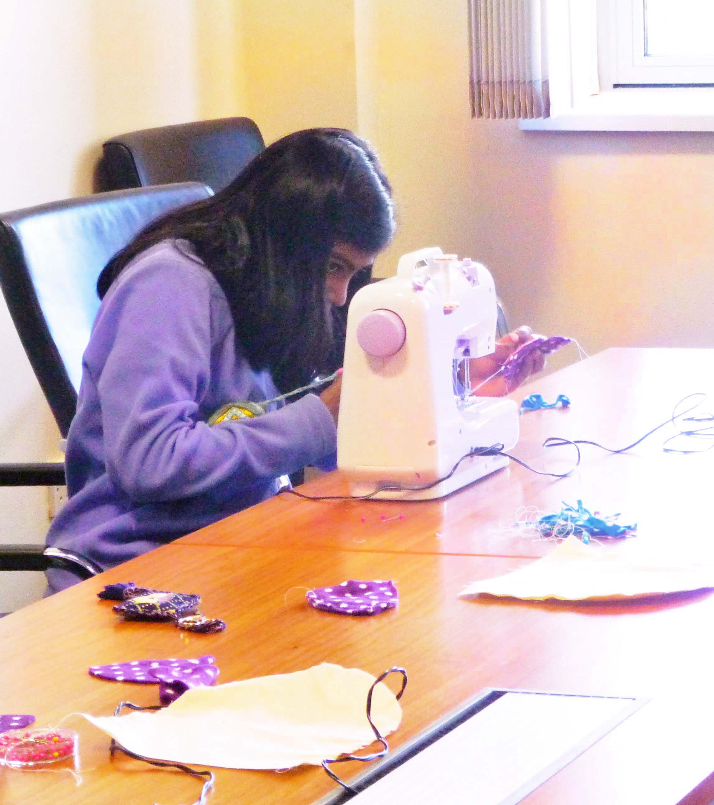 Grace is concentrating on machine sewing some ears