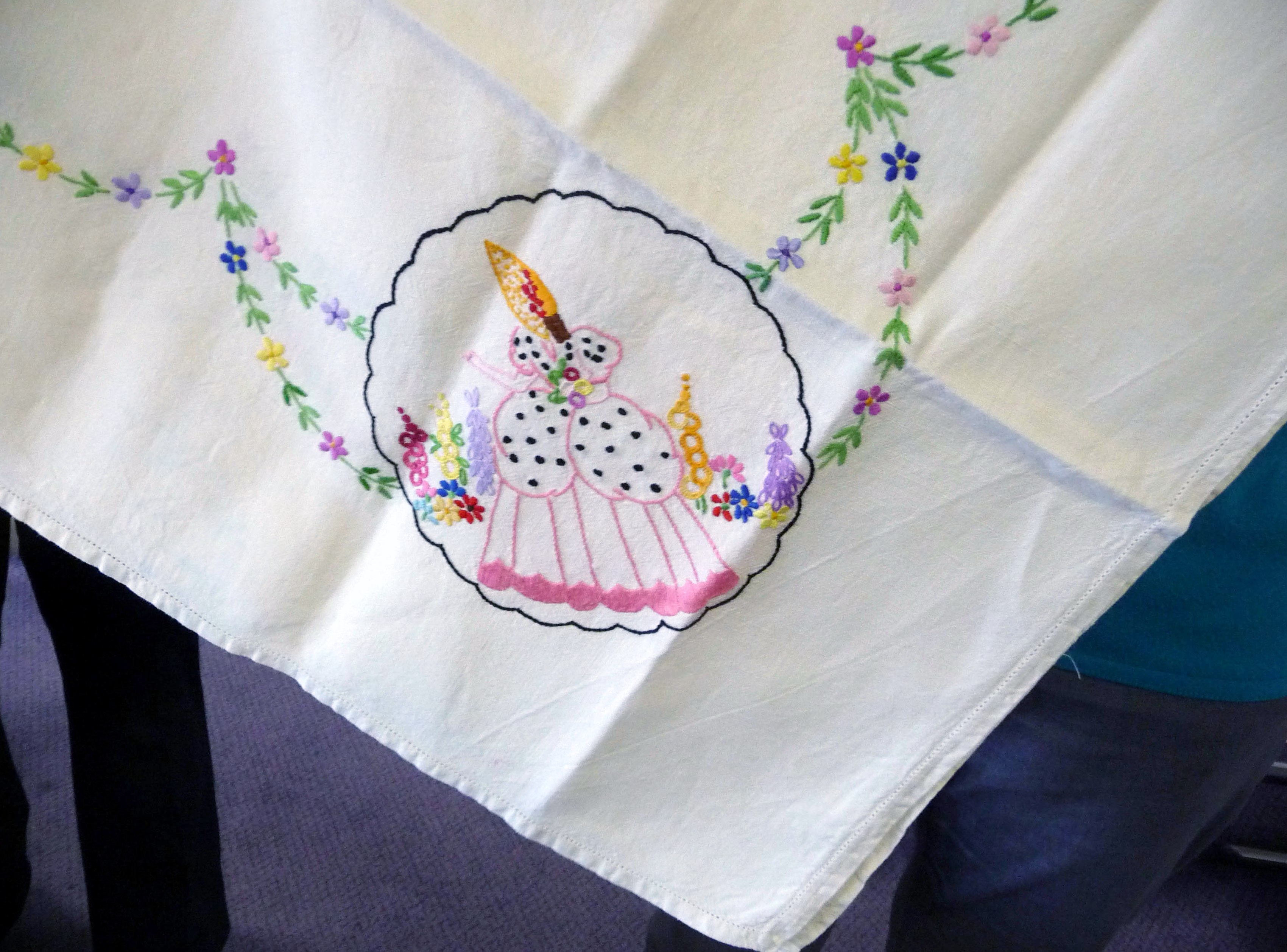Val is showing our YE group a very old embroidered tablecloth (detail)