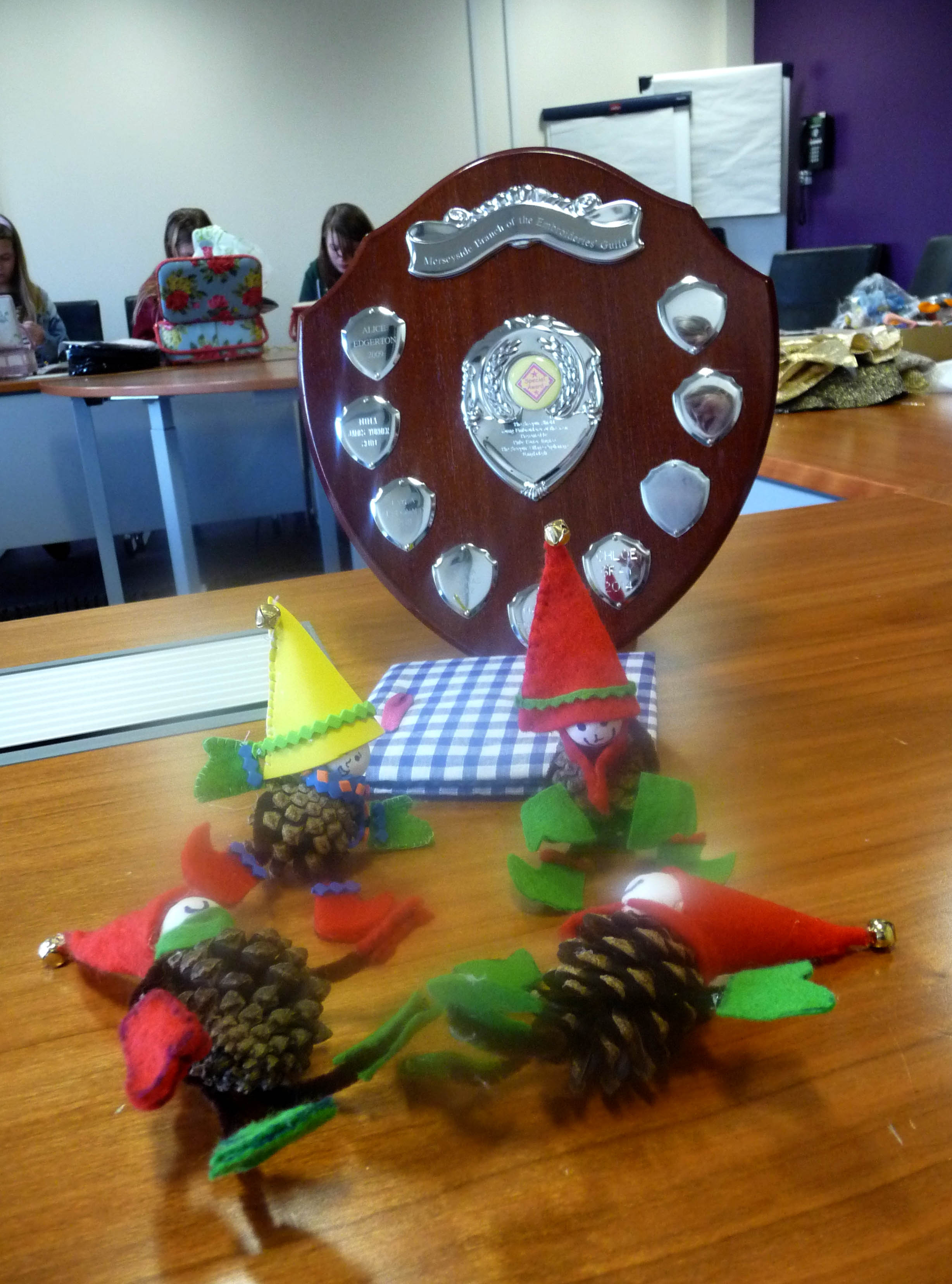some little elves made from pinecones and the Sreepur shield which is awarded to Merseyside Young Embroiderer of the Year