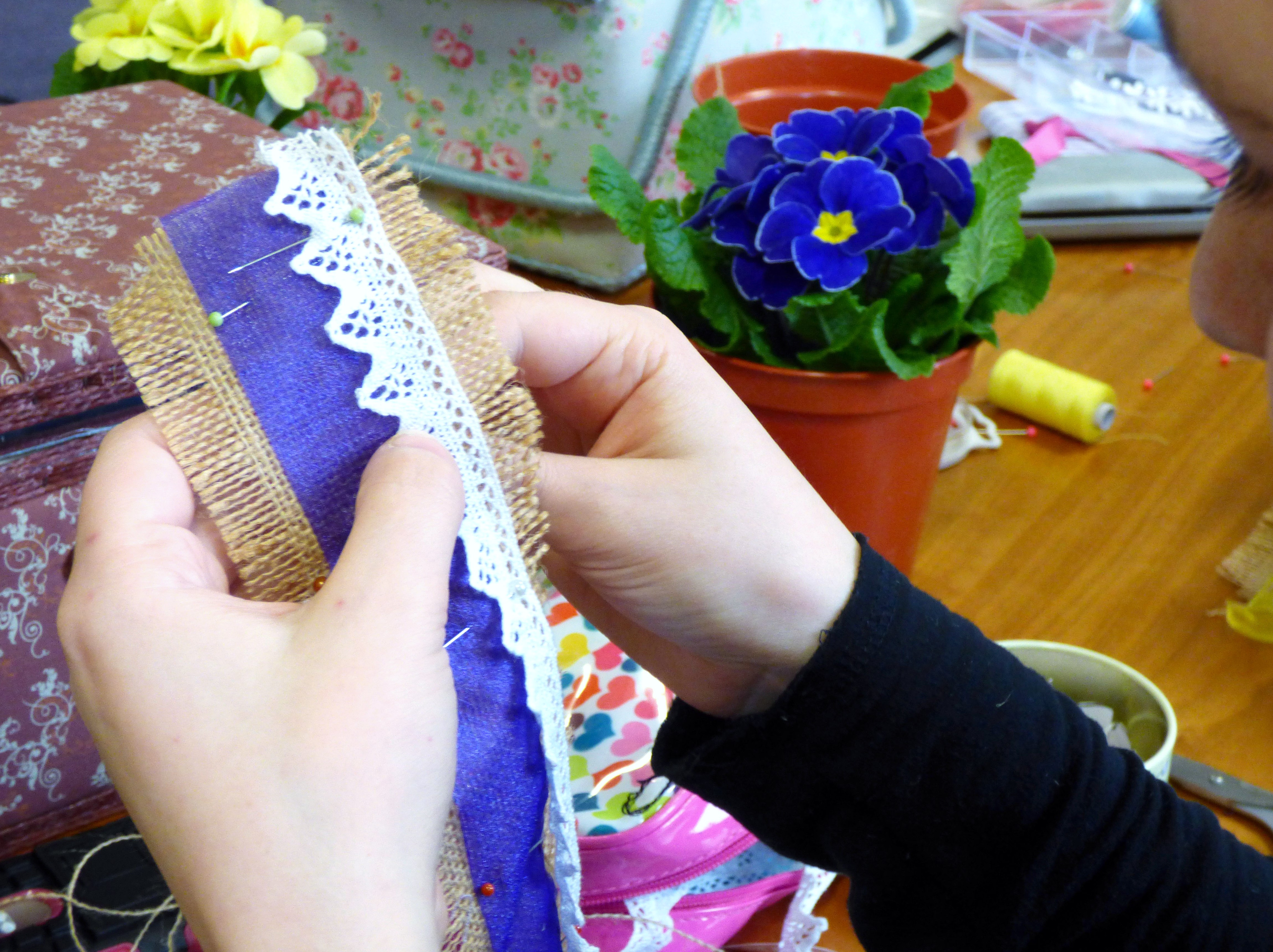 Chloe is decorating her plant pot band with lace and chiffon