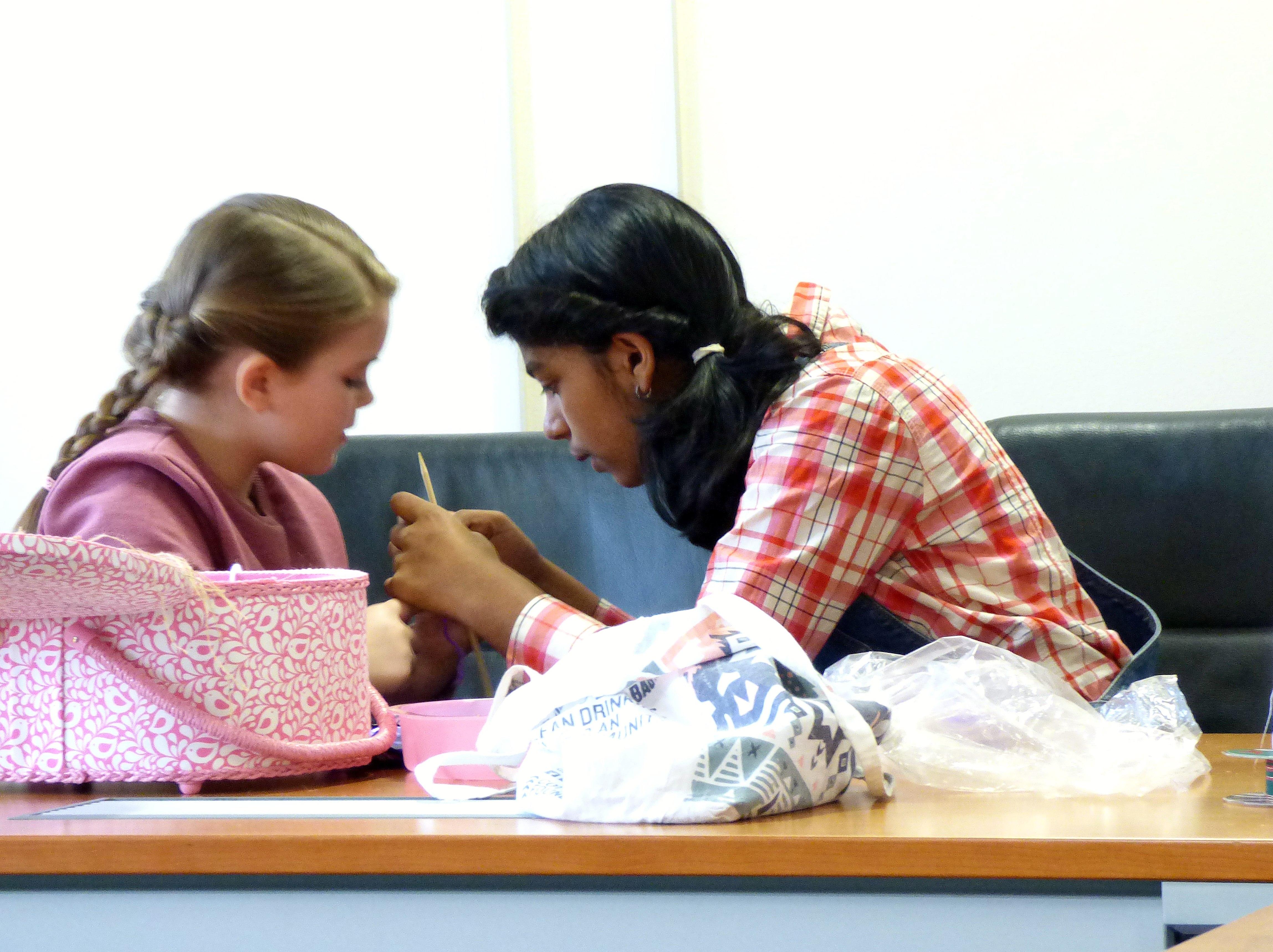 Grace is teaching Bella to knit