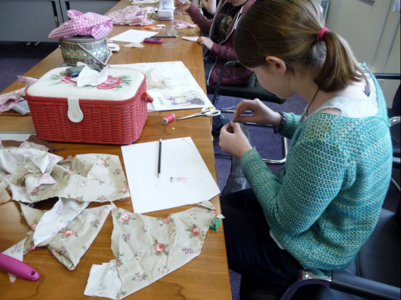 the older girls are learning how to make a stuffed toy with using a paper pattern