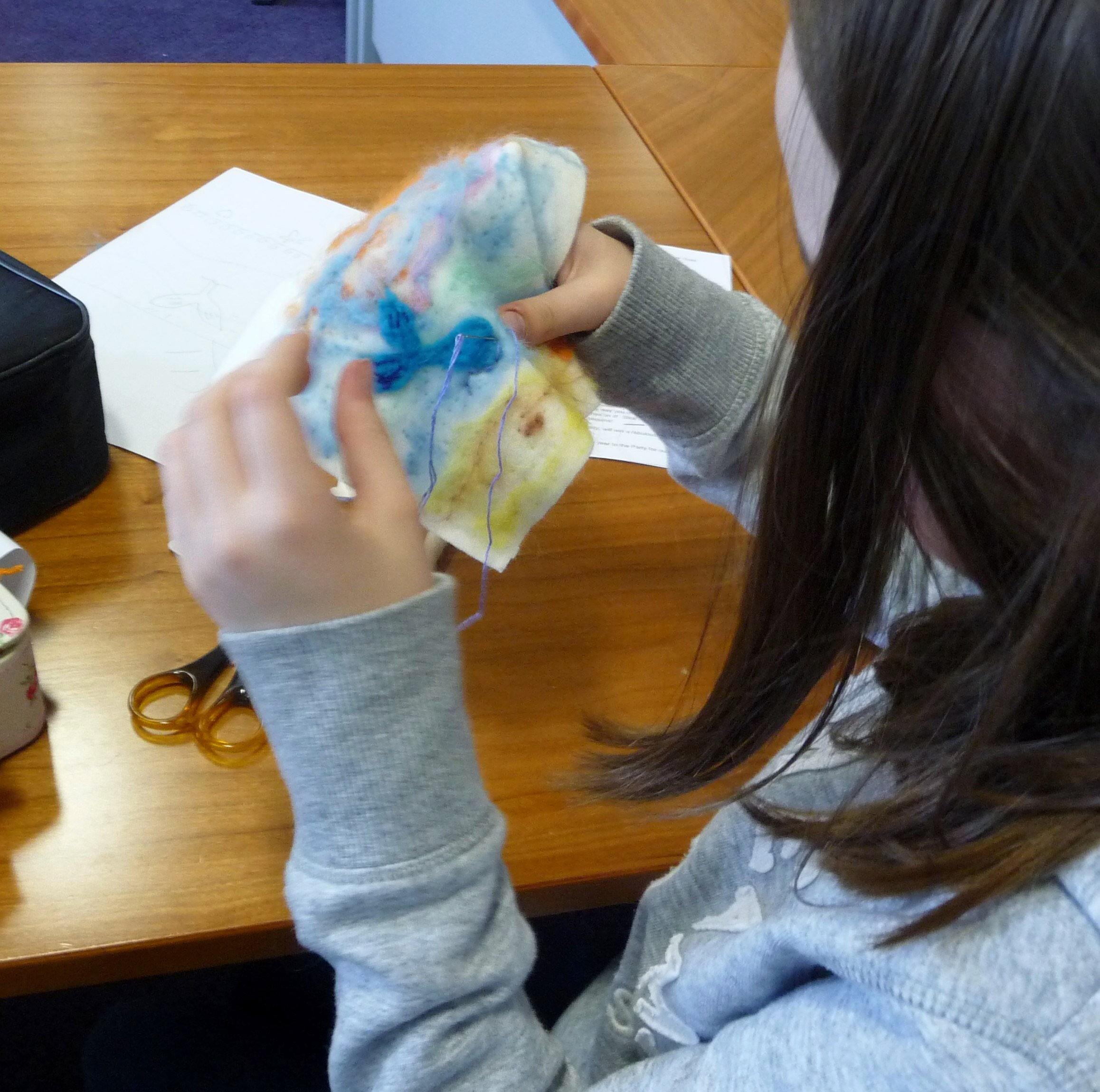 Ruby is stitching her whale in the needlefelted seascape