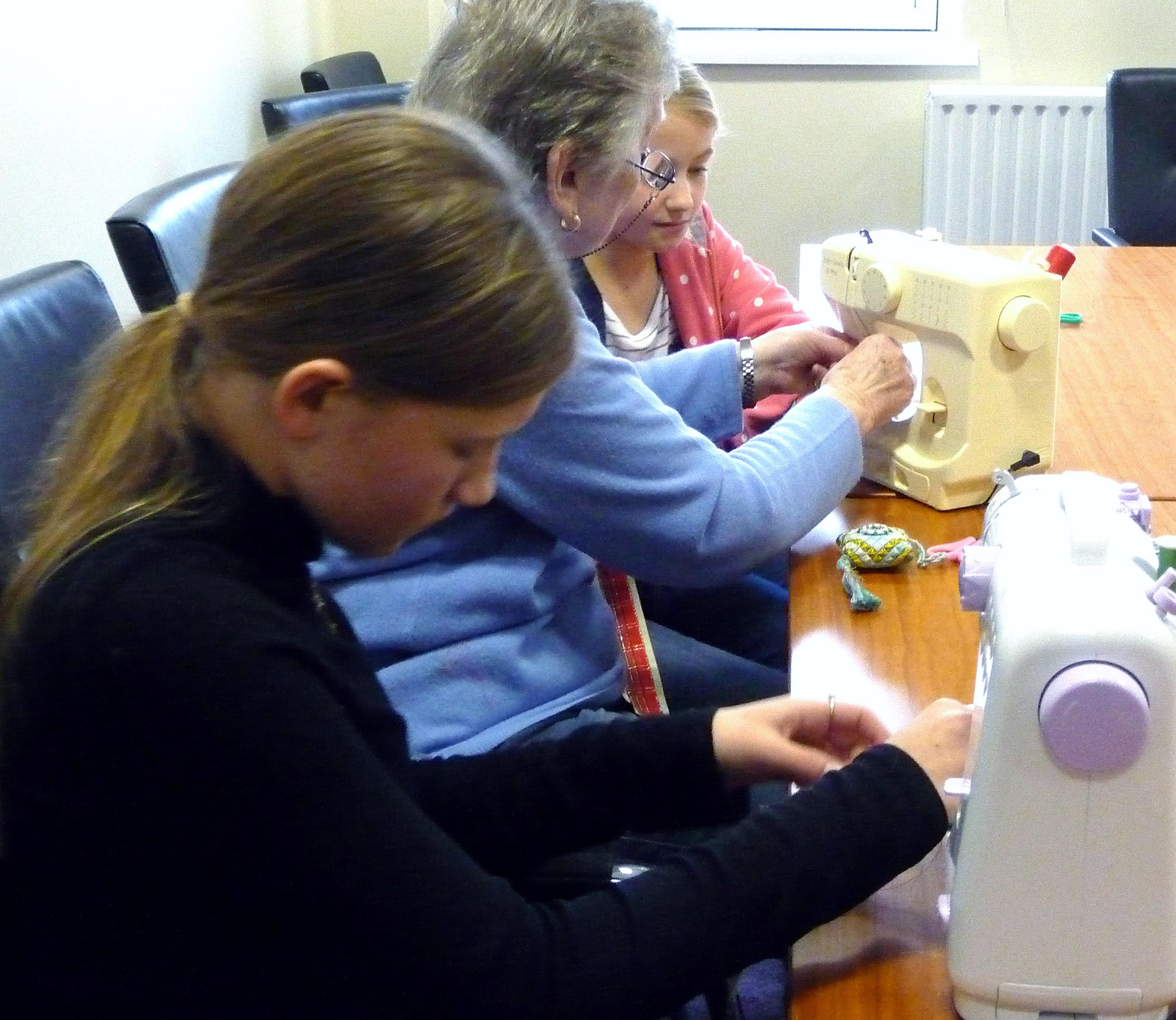 Val is helping Emma with the sewing machine at our Nov 2015 YE meeting