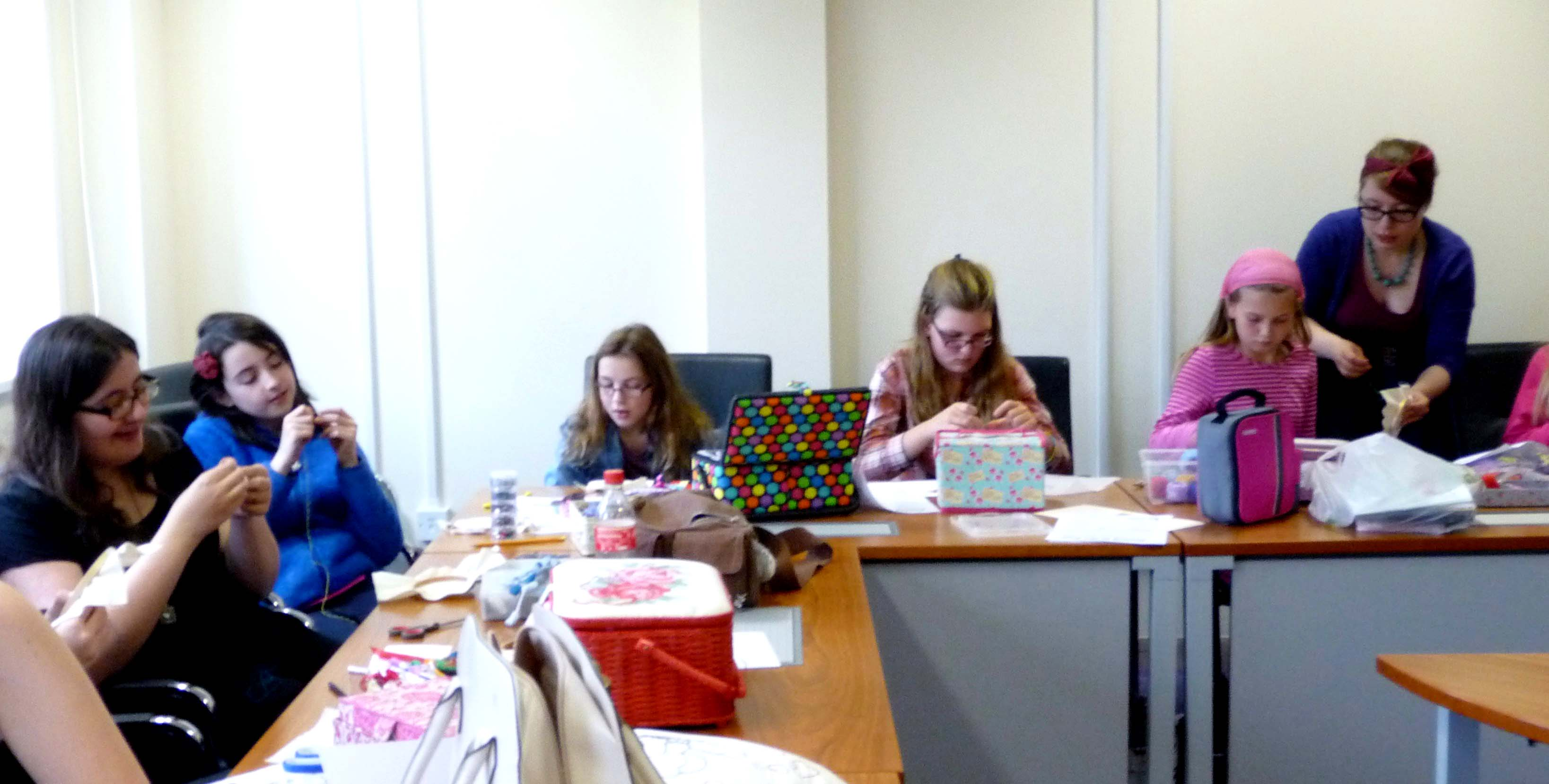 the girls are working hard on their embroideries, assisted by Becky Waite