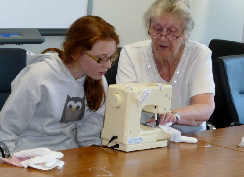 Val is showing Orla how to sew up her doll