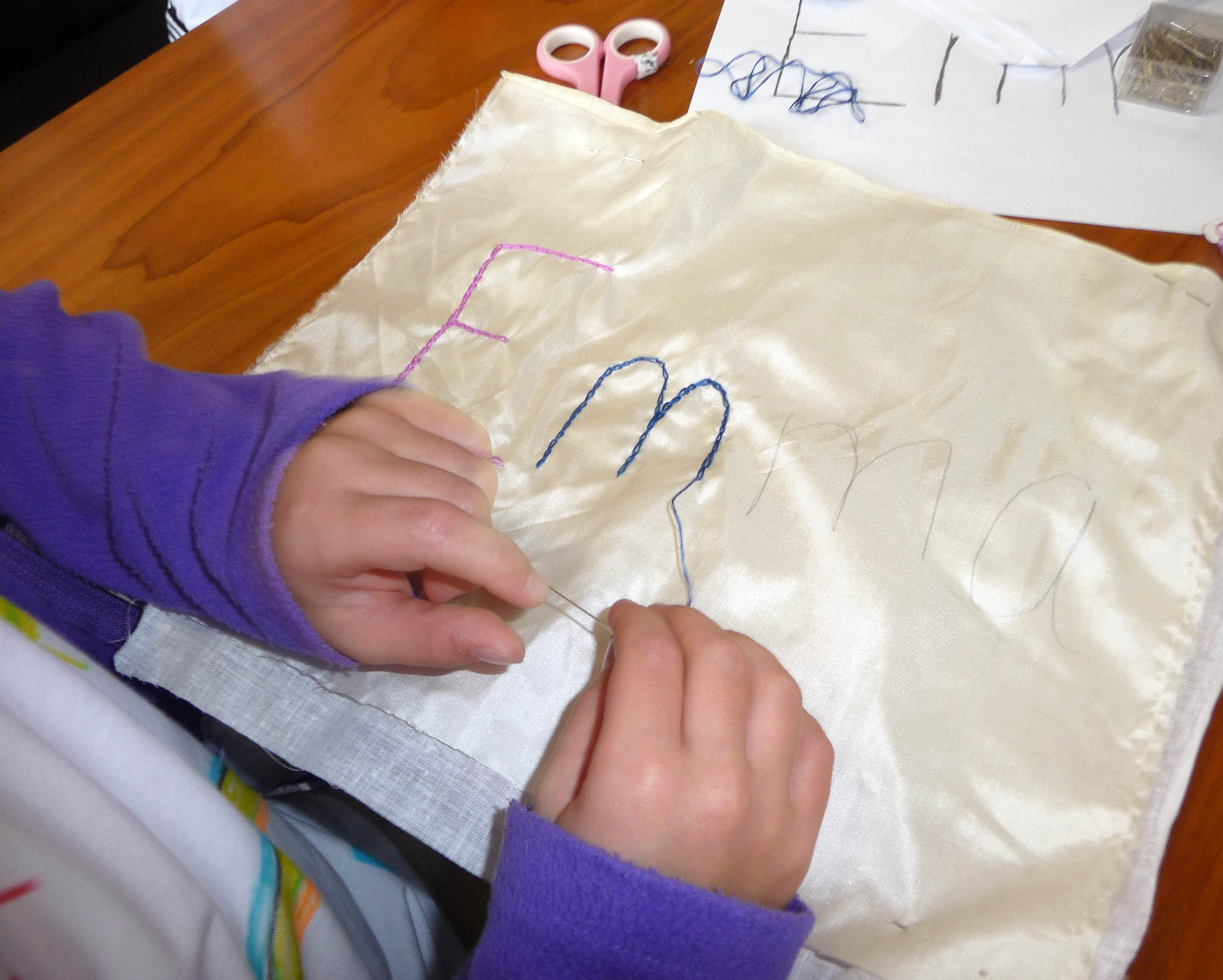 Emma is embroidering her name with chain stitch