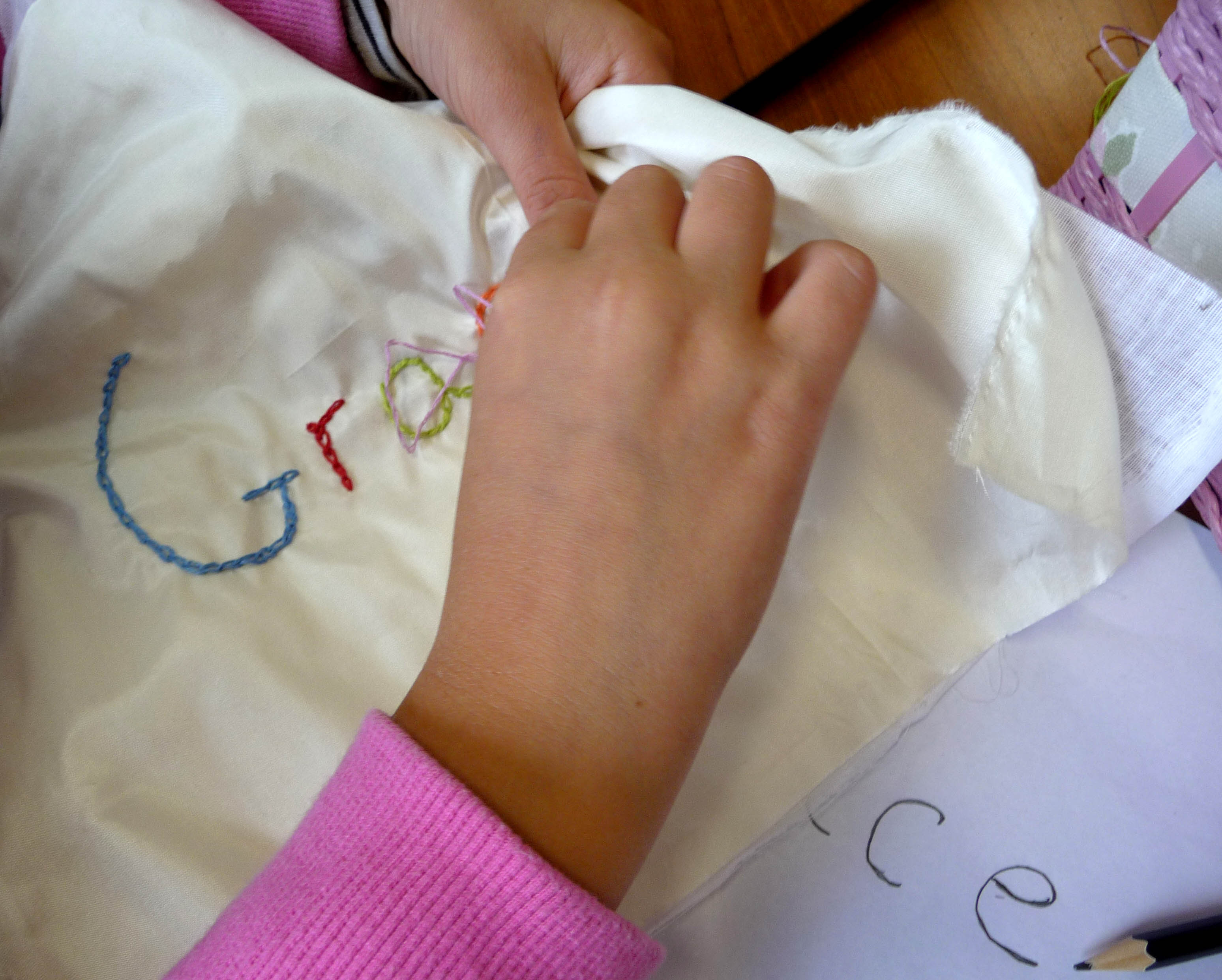 Grace is using a variety of colours to embroider her name