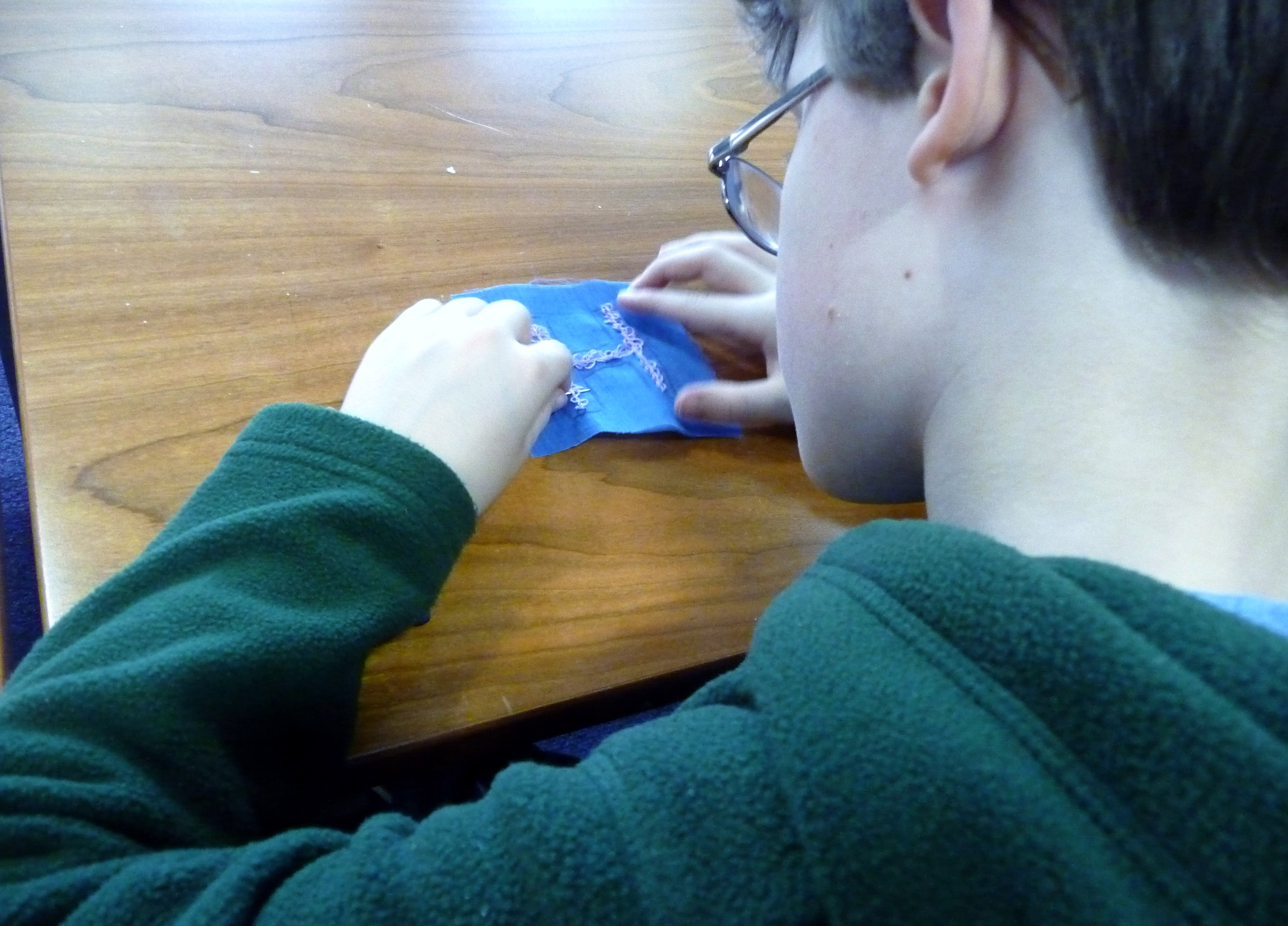 Fionn is concentrating on embellishing his letter with whip stitch