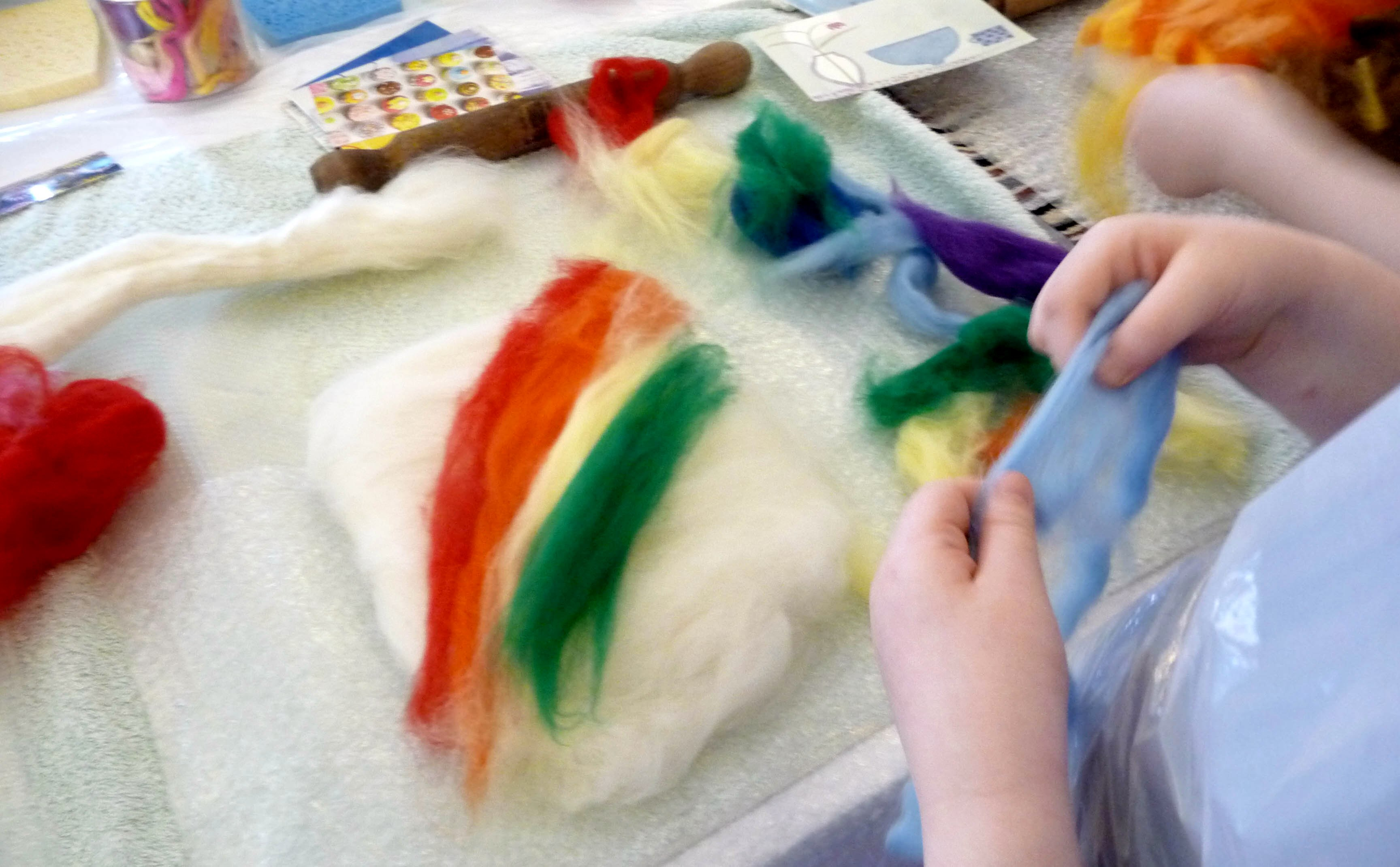 laying down the coloured wool layer. This picture will form a rainbow
