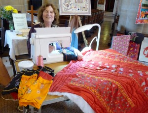 Norma is quilting some strips of fabric, hand embroidered in Sreepur, to make a quilt