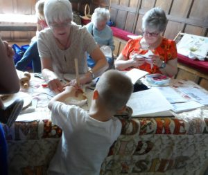 a young visitor is having a go at stitching with MEG at National Stitch Day @ Speke Hall 2019